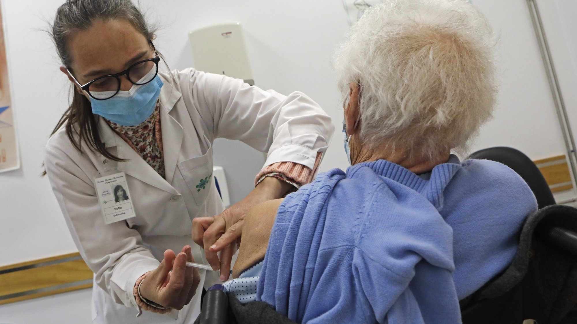 """Um idoso é vacinado contra a covid-19 por um profissional de saúde no Centro de Saúde de Penalva do Castelo, 12 de março de 2021. Idosos residentes em Penalva do Castelo, distrito de Viseu, e Fornos de Algodres, distrito da Guarda, encaram a vacinação como forma de combater a """"guerra"""" que o mundo trava contra a covid-19. (ACOMPANHA TEXTO DA LUSA DO DIA 27 DE MARÇO DE 2021). MIGUEL PEREIRA DA SILVA/LUSA"""