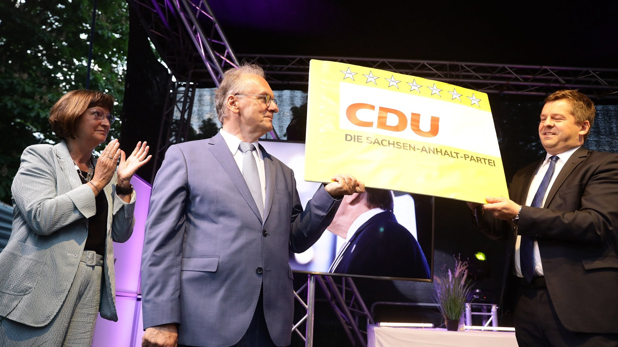 epa09251925 The leading candidate of the German Christian Democratic Party (CDU), Reiner Haseloff (C), his wife Gabriele (L) and the leader of the Saxony-Anhalt CDU, Sven Schulze, hold a poster with the inscription 'CDU, The Saxony-Anhalt Party',  at the election results party of the CDU following the Saxony-Anhalt state elections in Magdeburg, Germany, 06 June 2021. The regional election in Germany's federal state of Saxony-Anhalt is the last before general elections in September and is considered a trend indicator.  EPA/FILIP SINGER
