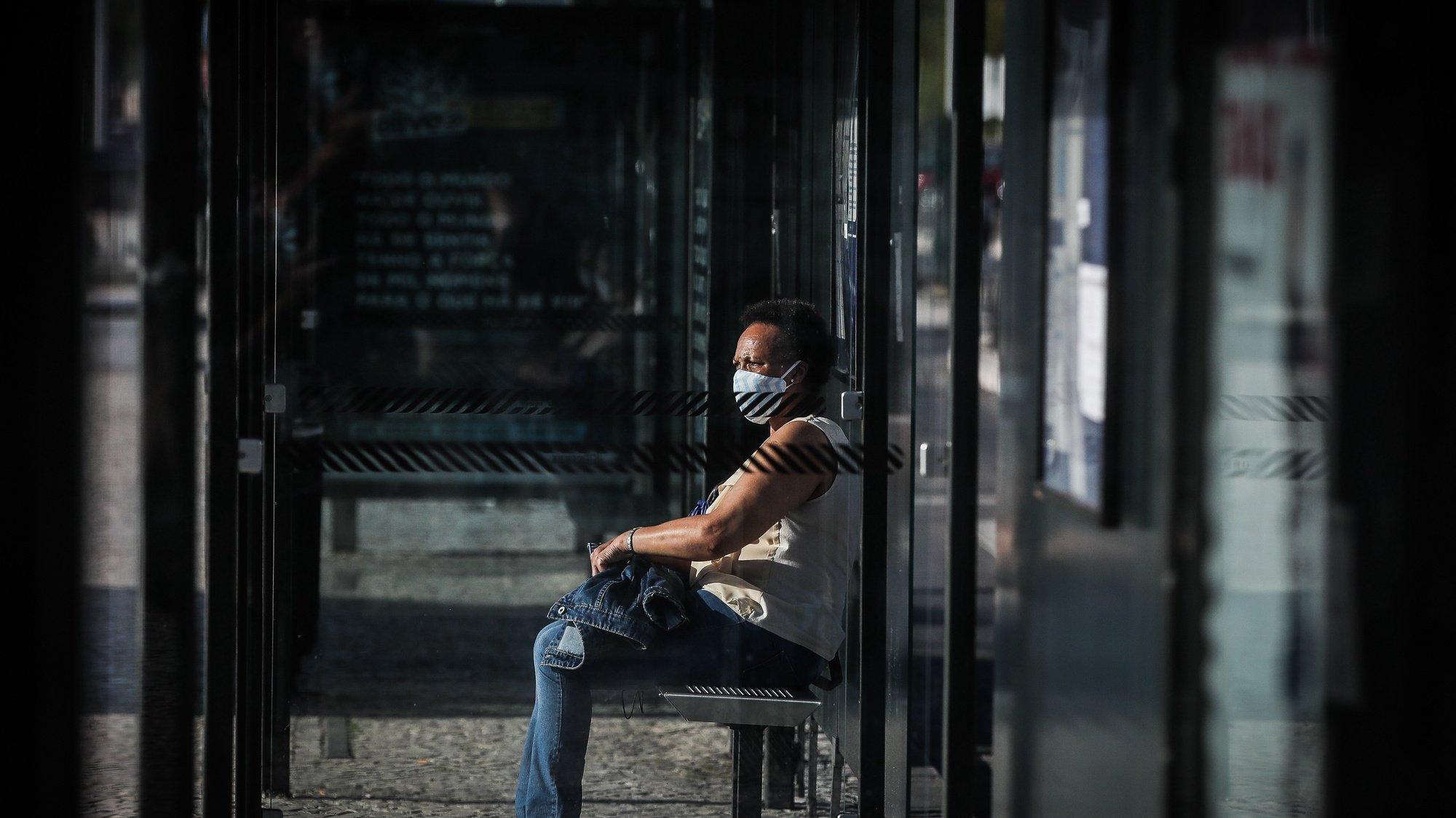 Uma pessoa espera por um autocarro dos Transportes Sul do Tejo (TST), em Cacilhas, Almada, 20 de maio de 2020. O transporte rodoviário foi reforçado com a entrada do segunda fase do desconfinamento devido à pandemia da covid-19, apesar disso as carreiras continuam com poucas pessoas o que contrasta com a grande utilização dos transportes fluviais da Transtejo/Soflusa. (ACOMPANHA TEXTO). MÁRIO CRUZ/LUSA