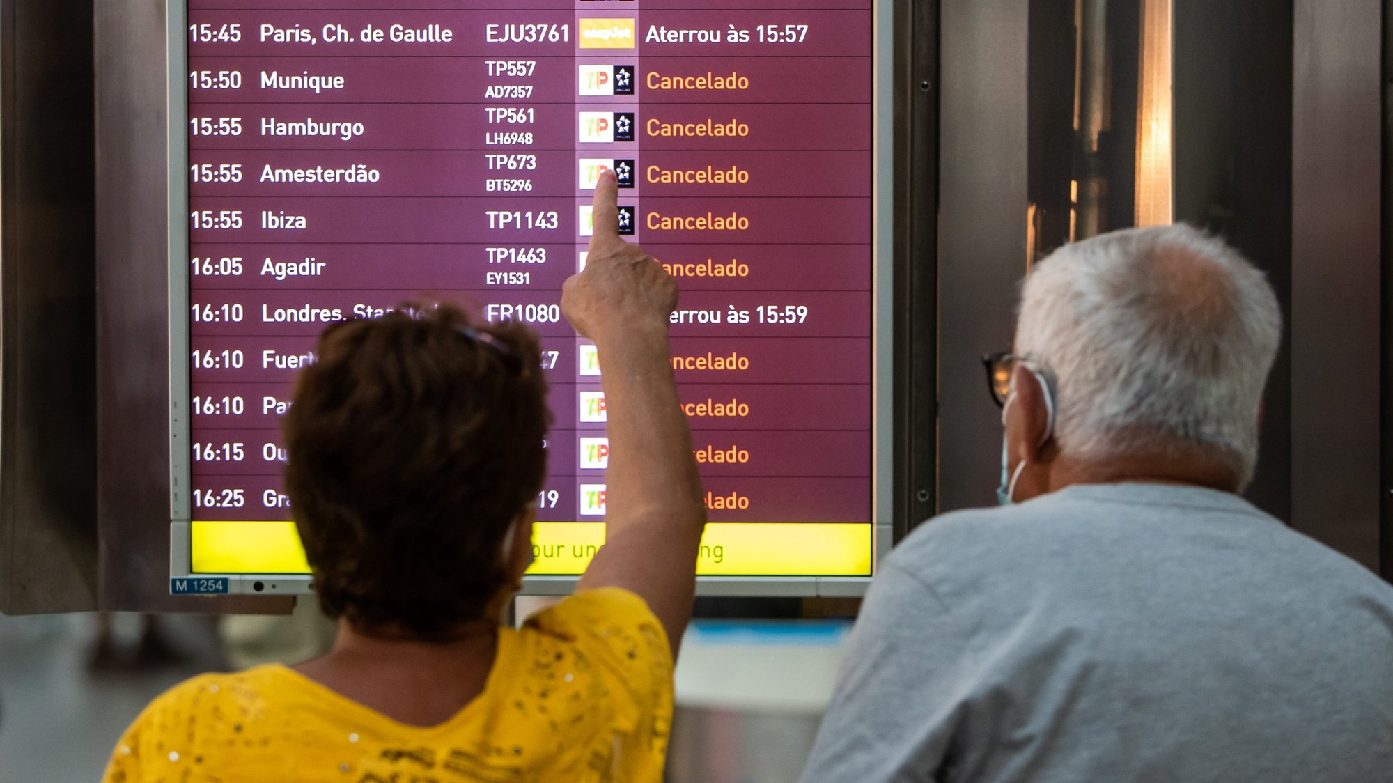 A woman points to a monitor with incoming flights to Lisbon, many of them canceled due to a strike of the handling company, Groundforce, which is causing major disruption in the Lisbon Airport, causing the cancelation of dozens of flights, in Lisbon, Portugal, 17 July 2021. Groundforce workers are protesting against colective dismissal of workers and low salaries. JOSE SENA GOULAO/LUSA