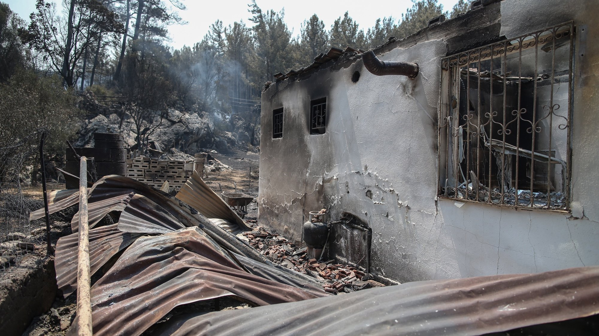 epa09382369 A view of a damaged house after a wildfire swept through at a rural of Marmaris district of Mugla, Turkey, 31 July 2021. According to a statement by the Turkish government's Disaster and Emergency Management Presidency (AFAD) released on 30 July 2021, at least three people lost their lives and some 271 others were affected by blazes that swept through the country's southern coast.  EPA/ERDEM SAHIN