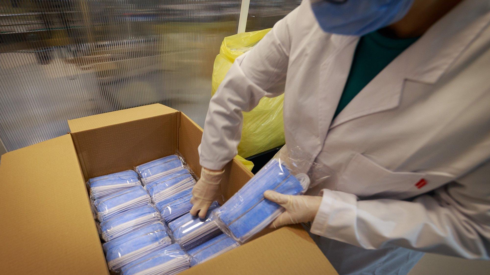Embalamento de máscaras no pavilhão instalado na Zona Industrial de Boticas que está nesta altura repleto de maquinaria ainda 'a brilhar', como máquinas de costura, máquinas que preparam o tecido para o fabrico de máscaras comunitárias, uma sala com uma linha de produção de máscaras cirúrgicas e ainda duas linhas de produção de álcool-gel, uma para embalagens de meio litro e outra para embalagens de cinco litros. O receio de despedir funcionários devido à pandemia de covid-19 levou um empresário de Boticas, do ramo do transporte de automóveis, a criar uma fábrica de produção de máscaras e álcool-gel que permitiu já contratar mais 11 pessoas, Boticas, 10 de fevereiro de 2021.  (ACOMPANHA TEXTO DO DIA 13 DE FEVEREIRO 2021) PEDRO SARMENTO COSTA/LUSA