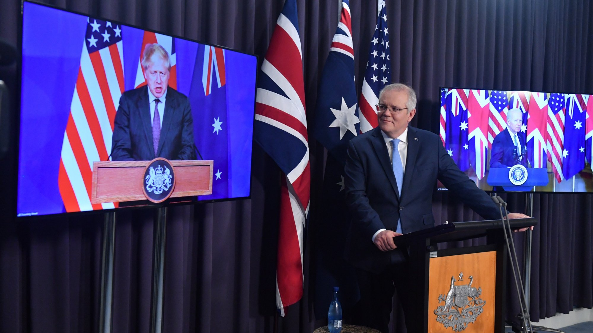 epa09470855 Britain's Prime Minister Boris Johnson, Australia's Prime Minister Scott Morrison (C) and US President Joe Biden attend a joint press conference via audio visual link (AVL) from The Blue Room at Parliament House in Canberra, Australian Capital Territory, Australia, 16 September 2021. Australia, the United Kingdom and the United States agreed to the creation of a trilateral security partnership to be known as AUKUS.  EPA/MICK TSIKAS AUSTRALIA AND NEW ZEALAND OUT