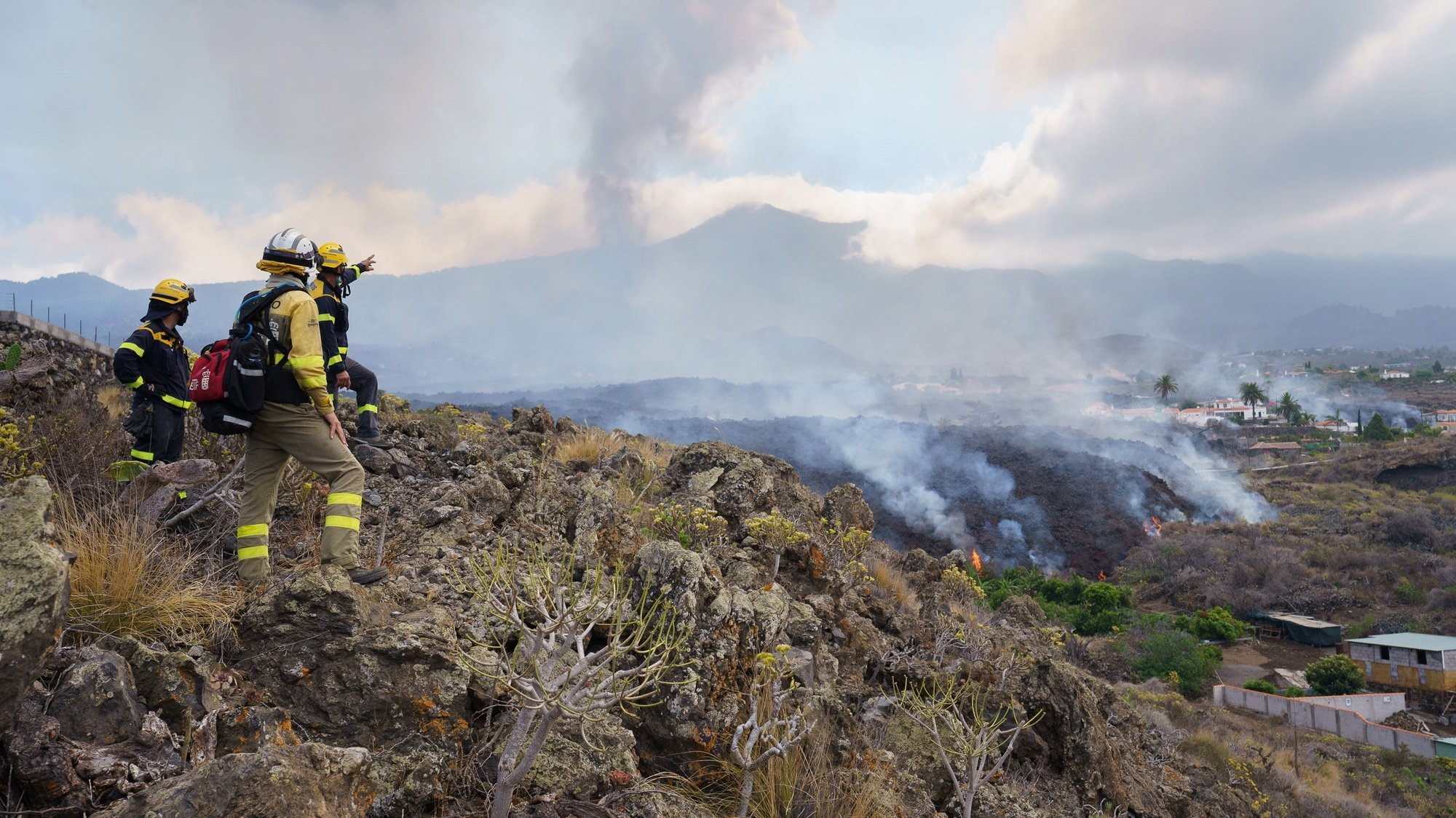 epa09479206 Firemen look at the lava flow from the Cumbre Vieja volcano as it moves towards the neighborhood of Todoque, in the municipality of Los Llanos de Aridane, after all locals were evacuated, in La Palma, Canary Islands, Spain, 21 September 2021.The Cumbre Vieja volcano began to erupt in Montana Rajada in the municipality of El Paso on 19 September.  EPA/Ramon de la Rocha