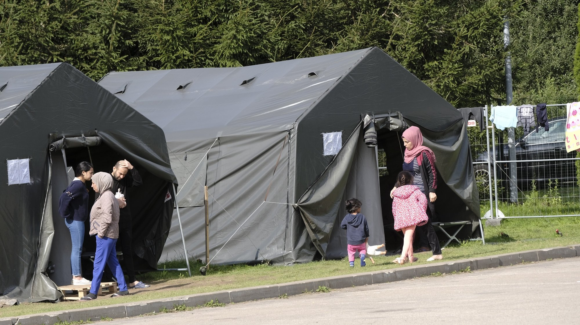 epa09428104 Migrants in the tent camp close to the Lithuania - Belarus border near Medininkai, Lithuania, 24 August 2021. More than 4,000 migrants have entered Lithuania illegally from neighbouring Belarus so far this year.  EPA/VALDA KALNINA