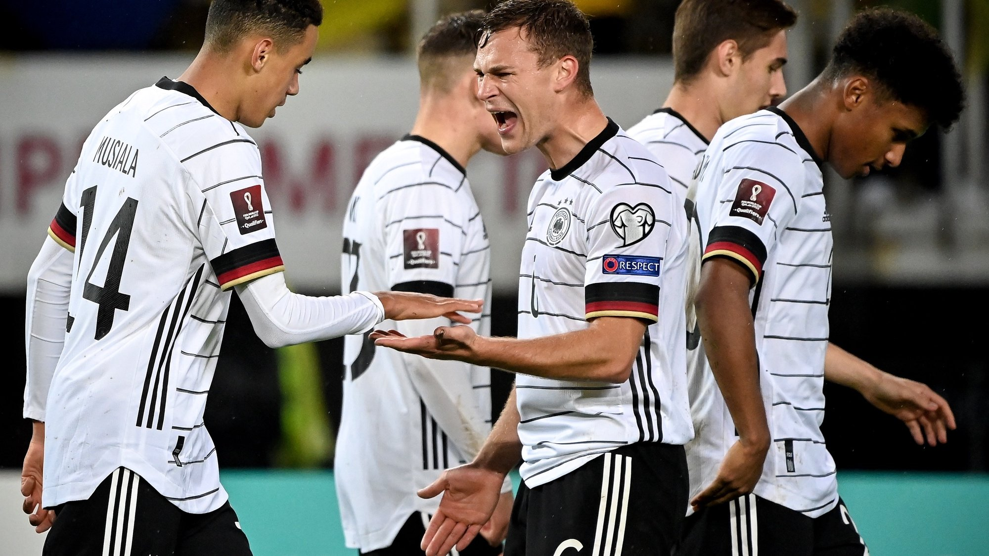 epa09519247 Germany's Jamal Musiala (L) celebrates with his teammate Joshua Kimmich (C) after scoring the 4-0 lead during the FIFA World Cup Qatar 2022 qualifying Group J soccer match between North Macedonia and Germany in Skopje, Republic of North Macedonia, 11 October 2021.  EPA/GEORGI LICOVSKI