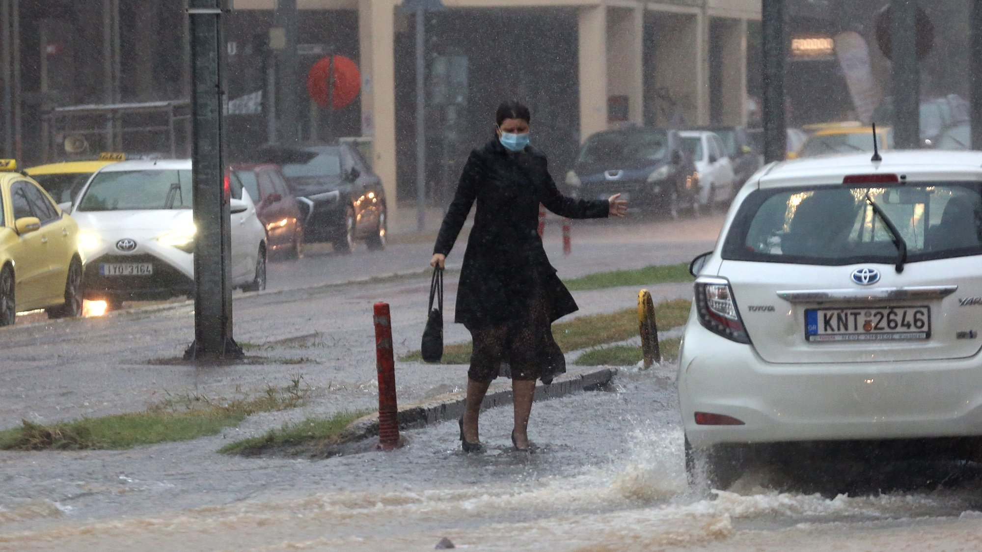 epa09523317 A woman makes her way under heavy rain in Athens, Greece, 14 October 2021. An emergency warning was sent to Attica residents from the 112 Emergency Communications Service on 14 October warning them of dangerous weather conditions and to avoid all non-essential travel.  EPA/ORESTIS PANAGIOTOU