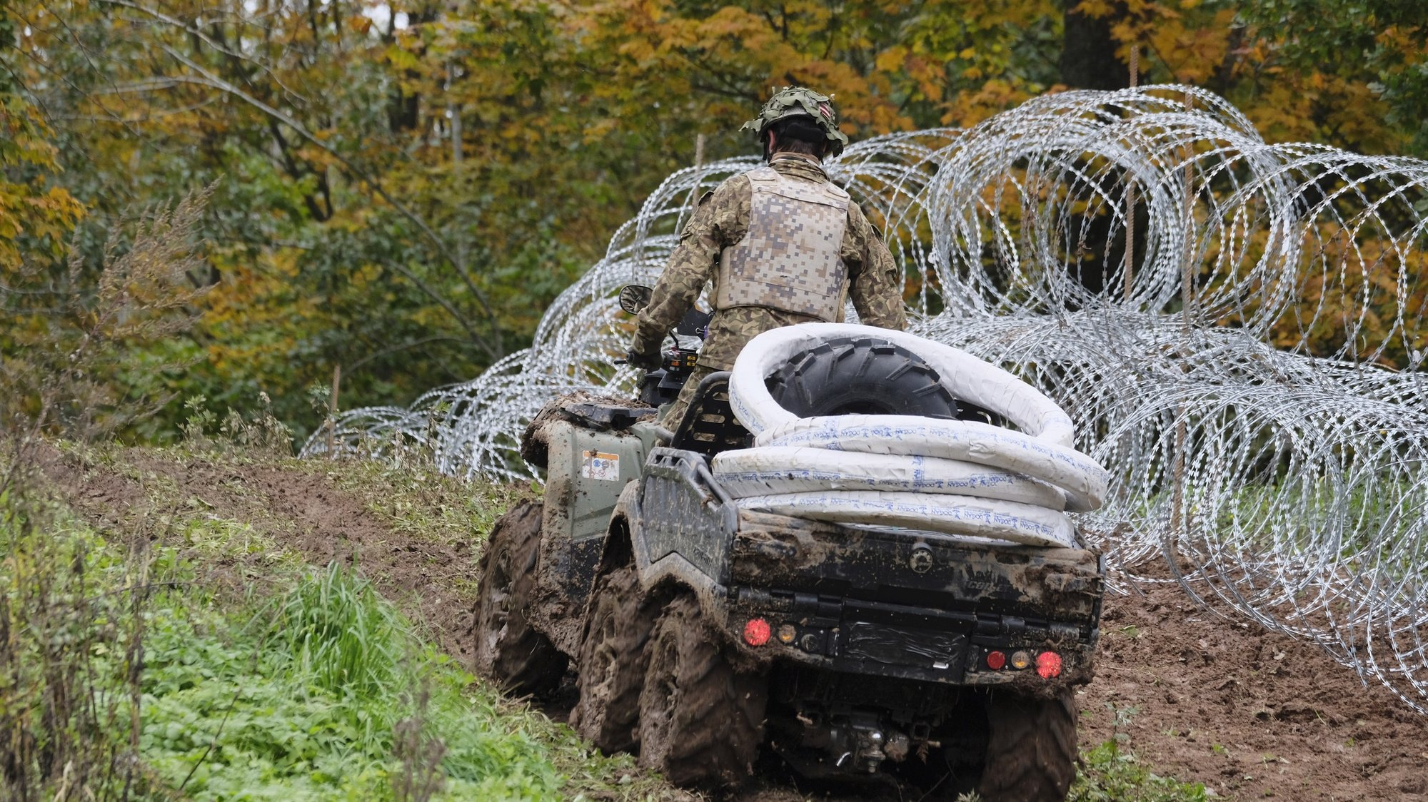 epa09493122 A soldier of Latvian National Armed Forces (NAF) patrols along a new barbed wire fence, donated by the Slovenian Ministry of Defense, on the state border with Belarus in Kraslava region, Latvia, 28 September 2021. This fence will cover the most critical border areas. Since August 10, a total of about 850 people have been reportedly deterred from crossing the state border illegally. According to the officials of Latvia, Lithuania and Poland, the pressure of migrants on the border is organized by Belarus.  EPA/VALDA KALNINA