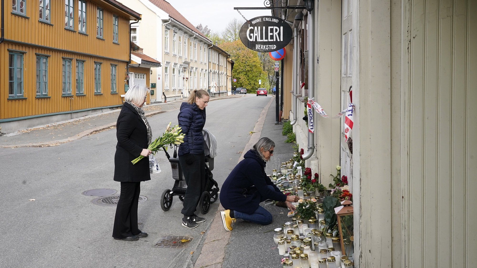 epa09529977 Three students by artist Hanne Englund lay flowers in front of her house in Kongsberg, Norway, 18 October 2021. A man has been arrested and charged with killing five and injuring three other people in Kongsberg center.  EPA/Terje Bendiksby  NORWAY OUT NORWAY OUT