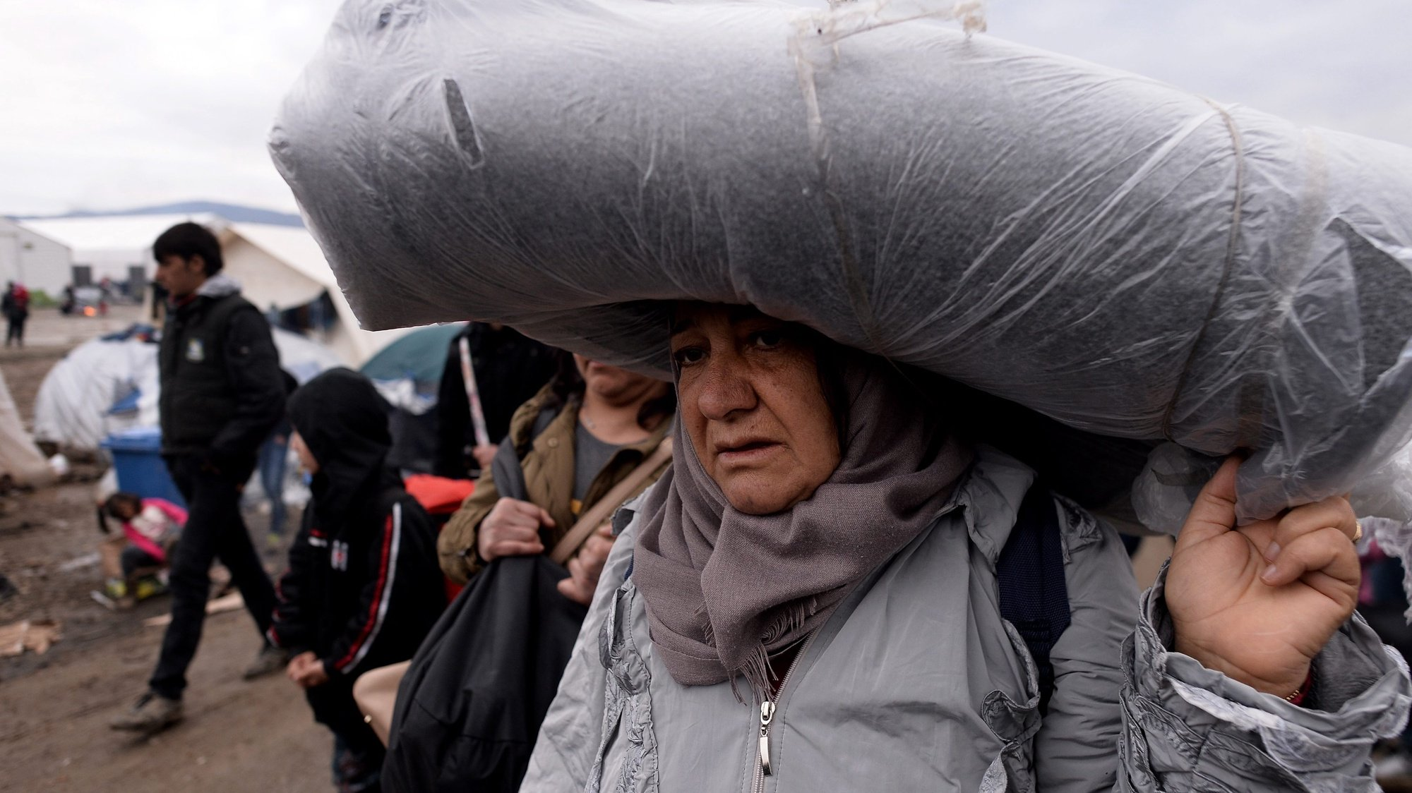epa05214864 A migrant carries a blanket, at a refugee camp at the border between Greece and the Former Yugoslav Republic of Macedonia (FYROM) near Idomeni, Northern Greece, 15 March 2016. Greek Prime Minister Alxis Tsipras on 15 March called on refugees to allow the Athens government to move them from the Idomeni camp to other reception centers, stressing that the borders are closed and will not be reopened in the near future. Greece has registered more than 44,000 migrants that are currently trapped due to entry restrictions already imposed by Macedonia in recent months, by denying entry to all those who are considered economic migrants, prohibiting the passage of Afghans, and finally denying entry to all Syrians and Iraqis who are not from combat areas.  EPA/NAKE BATEV  EPA/NAKE BATEV