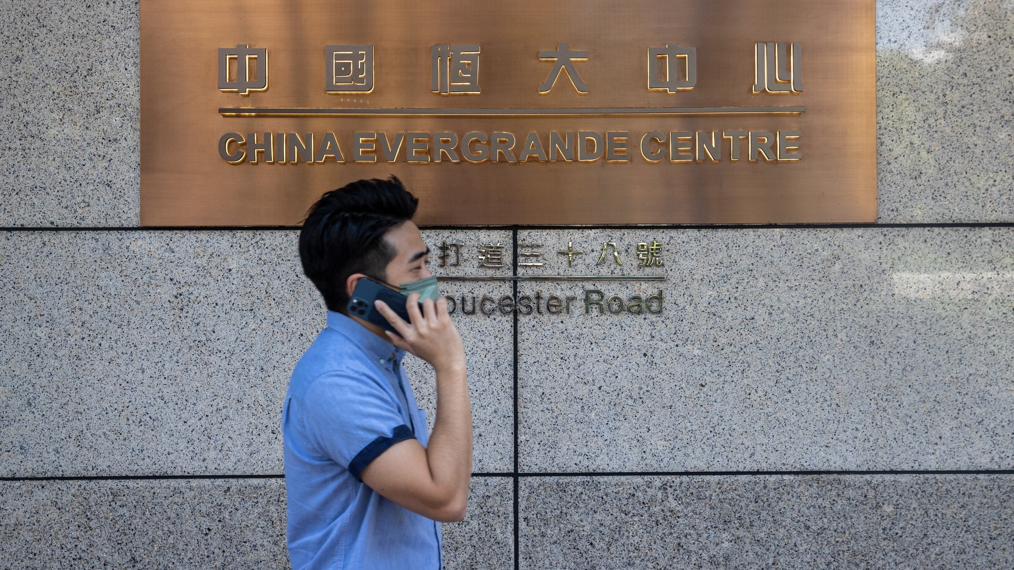 epa09504929 A man walks past the China Evergrande Centre in Hong Kong, China, 04 October 2021. China Evergrande's property management unit suspended shares trading in Hong Kong as the Shenzhen-based company has more than 300 billion US dollar in liabilities.  EPA/JEROME FAVRE