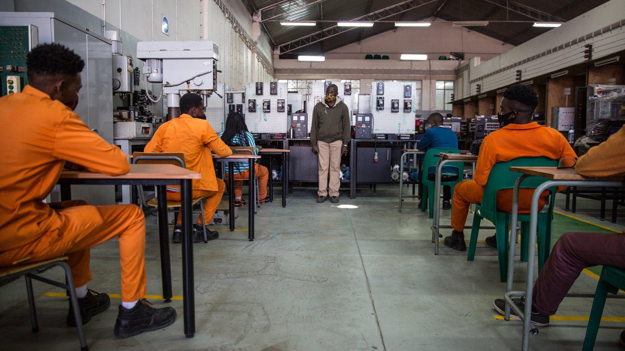 Alunos mantêm o distanciamento social e uso da máscara de proteção respiratória contra a covid-19 numa sala de aula no primeiro dia da reabertura do ensino superior e técnico com as novas normas de higiene e distanciamento social, no Instituto de Formação Profissional e Estudos Laborais Alberto Cassimo, em Maputo, Moçambique, 18 de agosto de 2020. O primeiro dia da retoma faseada às atividades em institutos e universidades moçambicanas começou a meio-gás em Maputo, com metade de estudantes por cada turma e aulas de orientações sobre as medidas de prevenção contra à pandemia da covid-19. RICARDO FRANCO/LUSA