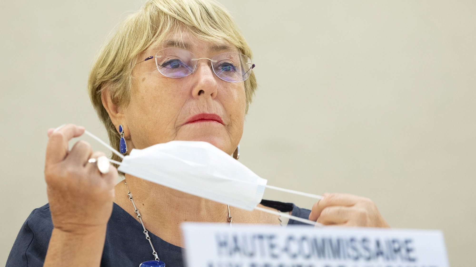 epa09465123 UN High Commissioner for Human Rights, Chilean Michelle Bachelet, removes her protective face mask prior her statement, during the 48th session of the Human Rights Council, at the European headquarters of the United Nation, in Geneva, Switzerland, 13 September 2021.  EPA/SALVATORE DI NOLFI