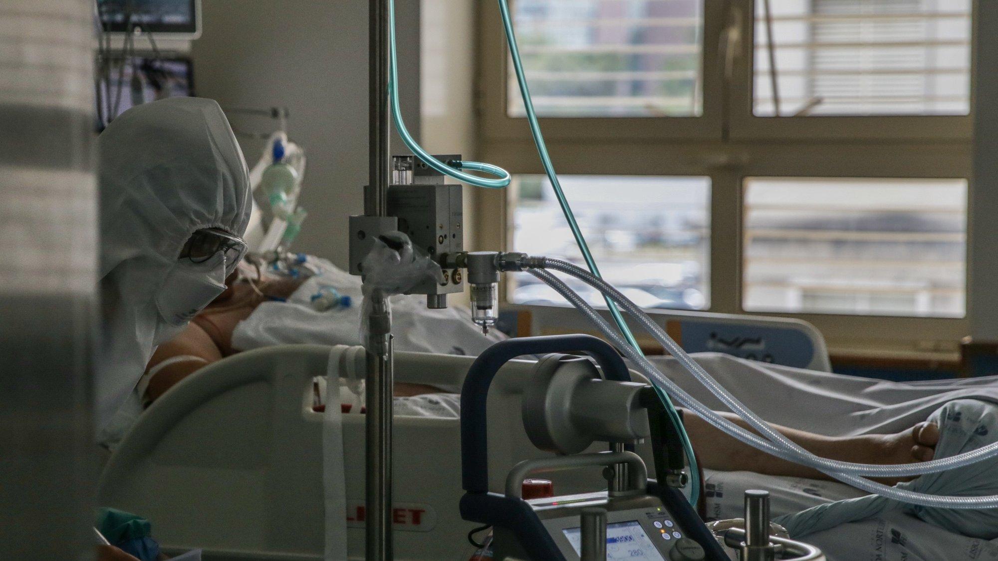 Uma enfermeira cuida de um paciente hospitalizado na Unidade de Cuidados Intensivos Covid 19 do Hospital Santa Maria em Lisboa, 27 de outubro de 2020. A urgência dedicada aos casos suspeitos de covid-19 do Hospital Santa Maria, em Lisboa, reflete a evolução da pandemia em Portugal com doentes a avolumarem-se à porta para realizar o teste e no interior a capacidade quase esgotada. O medo de perder o emprego leva muitos doentes com covid-19 a esconderem que estão infetados e a continuar a trabalhar, disseminando a doença que, nesta fase, começa a ser um caso também social e que leva a muitos internamentos no Santa Maria. (ACOMPANHA TEXTO DA LUSA DE 30 DE OUTUBRO DE 2020) TIAGO PETINGA/LUSA