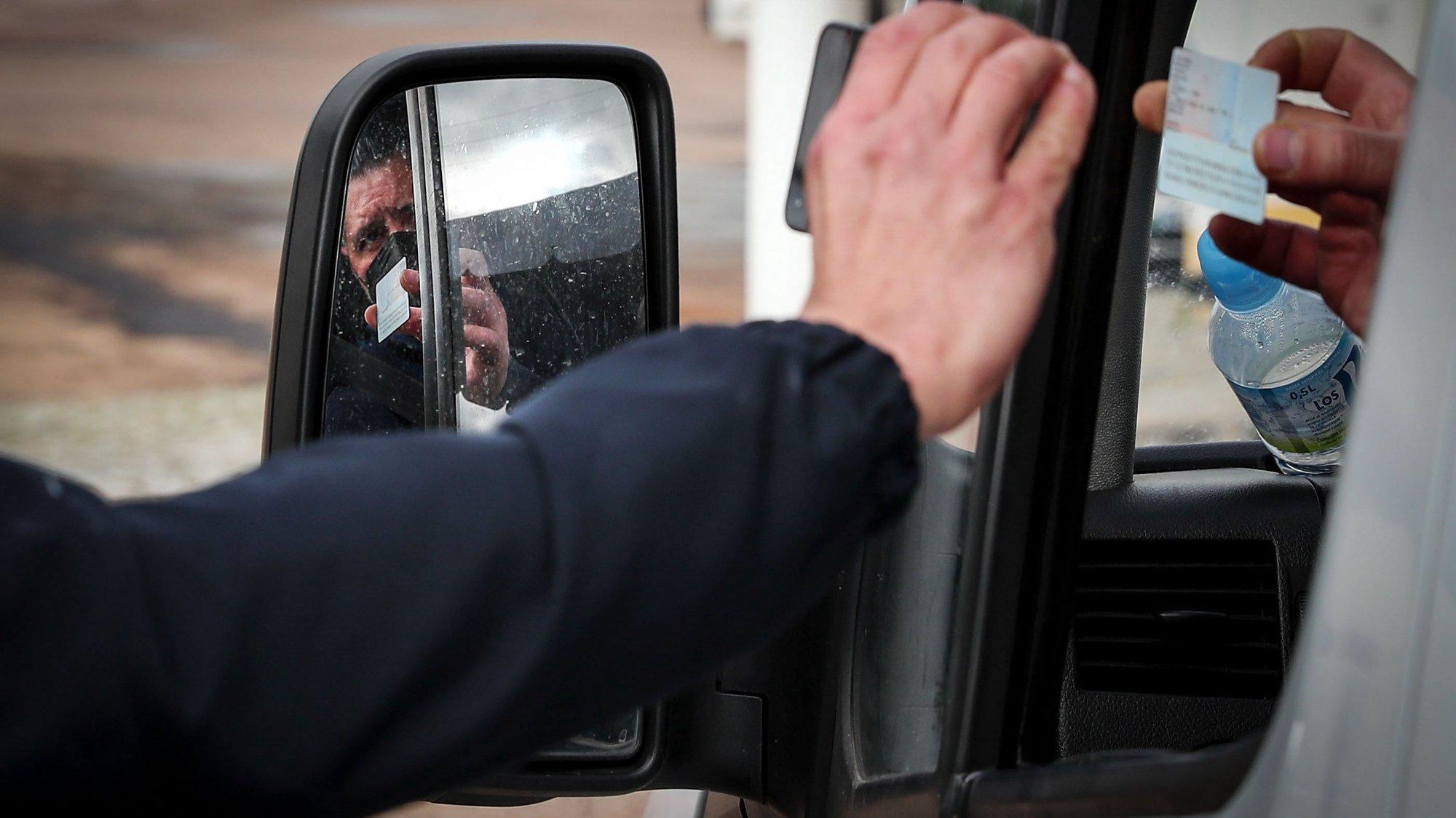 Um agente do Serviço de Estrangeiros e Fronteiras (SEF) verifica a identificação de um automobilista com uma aplicação de smartphone do SEF durante uma operação de controlo na entrada em Portugal pela fronteira do Caia, Elvas,1 de fevereiro de 2021. As fronteiras foram repostas desde as 00:00 de domingo, dia 31 de janeiro, no âmbito das medidas para conter a propagação da covid-19 no território português. NUNO VEIGA/LUSA