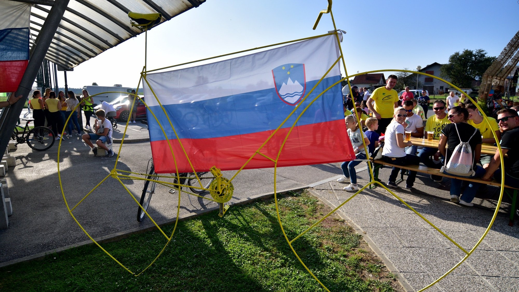 epa08684244 A yellow bike with the Slovenian flag as locals watch the broadcast of the 21st and last stage of the 2020 Tour de France cycling race, in Komenda, Slovenia, 20 September 2020. The village is the home town of cyclist Tadej Pogacar who wears the overall leader's yellow jersey before the last stage.  EPA/IGOR KUPLJENIK