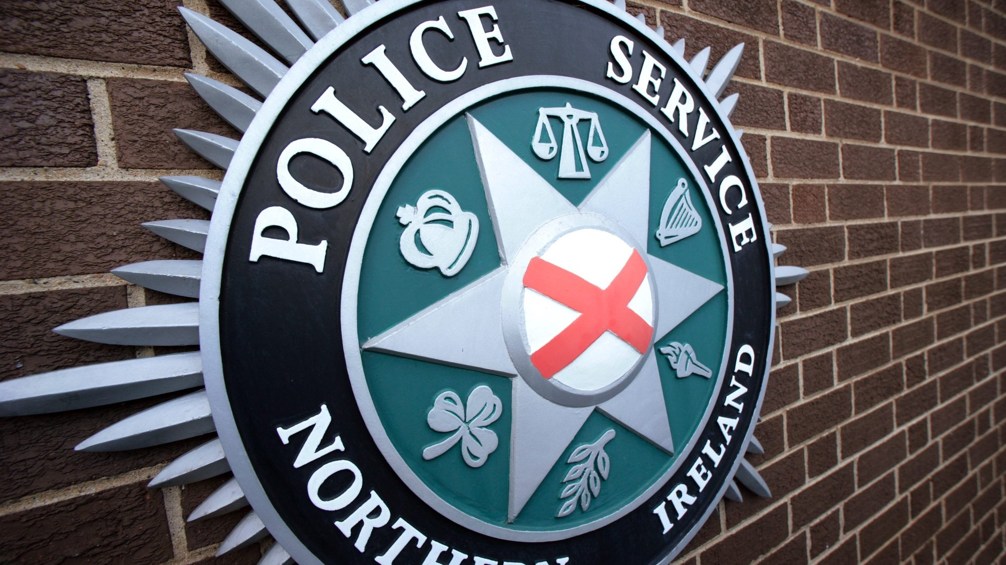 epa02018509 The PSNI (Police Service of Northern Ireland) badge outside Police Headquarters, east Belfast, Northern Ireland, on 05, Febuary 2010. A deal between Northern Ireland's biggest parties, the DUP and Sinn Fein, could see policing and justice powers devolved to Northern Ireland on 12 April 2010. A cross-community vote on devolving the powers will be held in the Northern Ireland Assembly on 09 March 2010.  EPA/PAUL MCERLANE