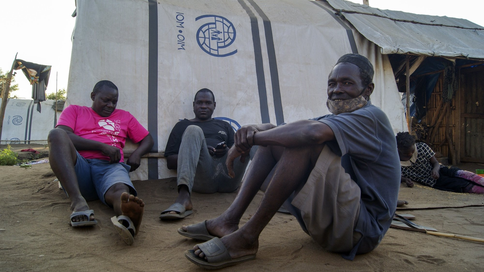 epa09417541 Men sit in one of the shelter camps in Metuge, a space housing displaced people fleeing armed violence in northern Mozambique, Cabo Delgado, Mozambique, 16 August 2021 (issued 17 August 2021). Following the attacks, which have terrorized Cabo Delgado province since 2017, there are more than 3,100 deaths, according to the ACLED conflict registration project, and more than 817,000 displaced people, according to Mozambican authorities.  EPA/LUISA NHANTUMBO