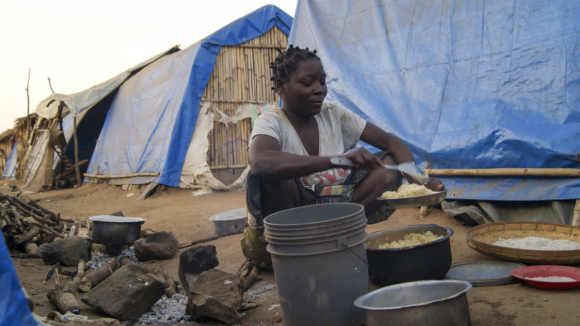 A woman prepares a meal in one of the shelter camps in Metuge, a space housing displaced people fleeing armed violence in northern Mozambique. Cabo Delgado, Mozambique, 16 August 2021 (issue on 17 August 2021). Following the attacks, which have terrorized Cabo Delgado province since 2017, there are more than 3,100 deaths, according to the ACLED conflict registration project, and more than 817,000 displaced people, according to Mozambican authorities. LUISA NHANTUMBO/LUSA