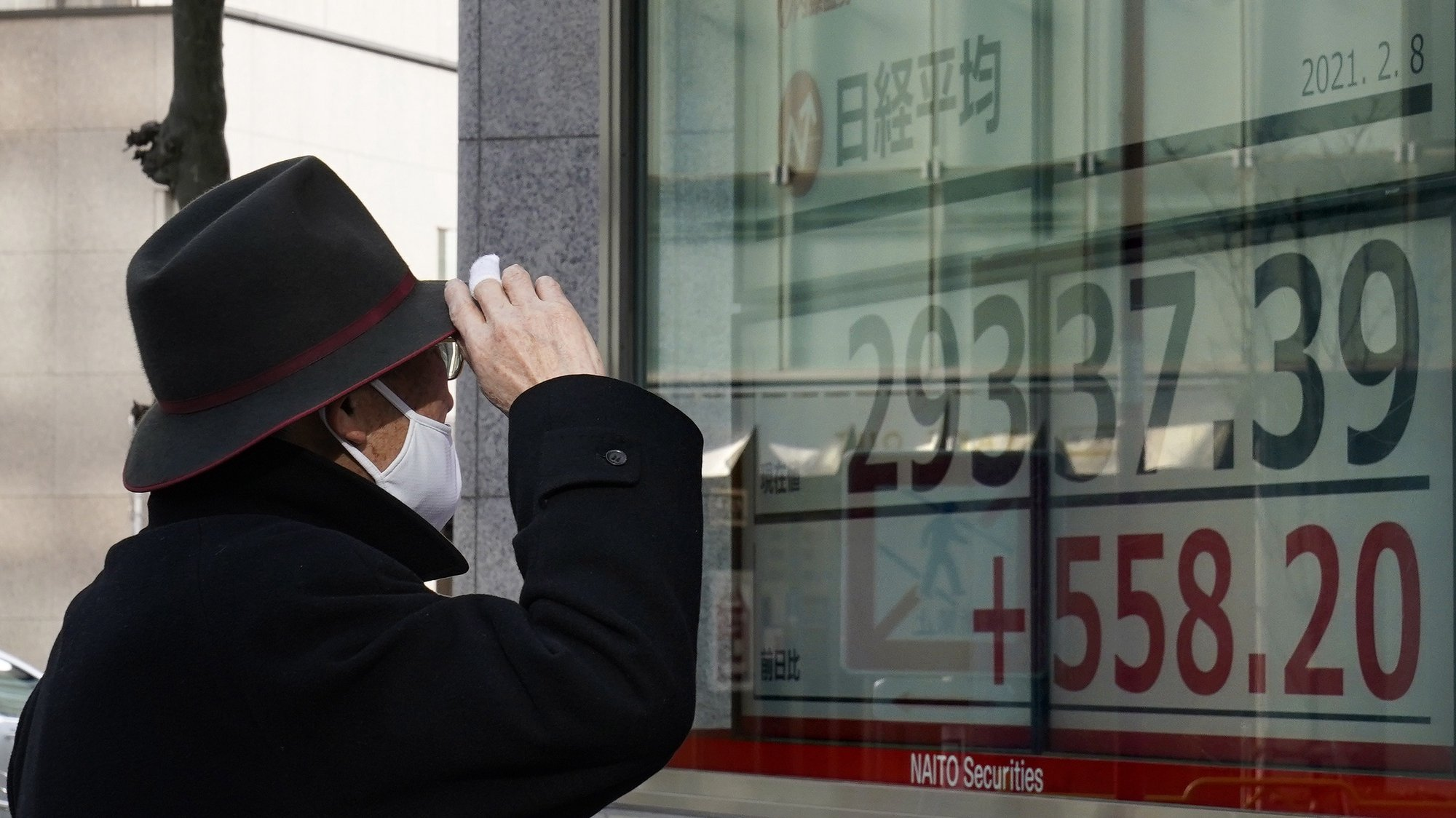 epa08995552 A pedestrian looks at a display showing Nikkei Stock Average during the afternoon trading session in Tokyo, Japan, 08 February 2021. Tokyo stocks climbed over 29,000 level for the first time in more than 30 years. The benchmark Nikkei Stock Average surged 609.31 points, or 2.12 per cent, to close at 29,388.50 on hope that US government may implement a new economic package for a breakthrough against the new coronavirus pandemic.  EPA/KIMIMASA MAYAMA