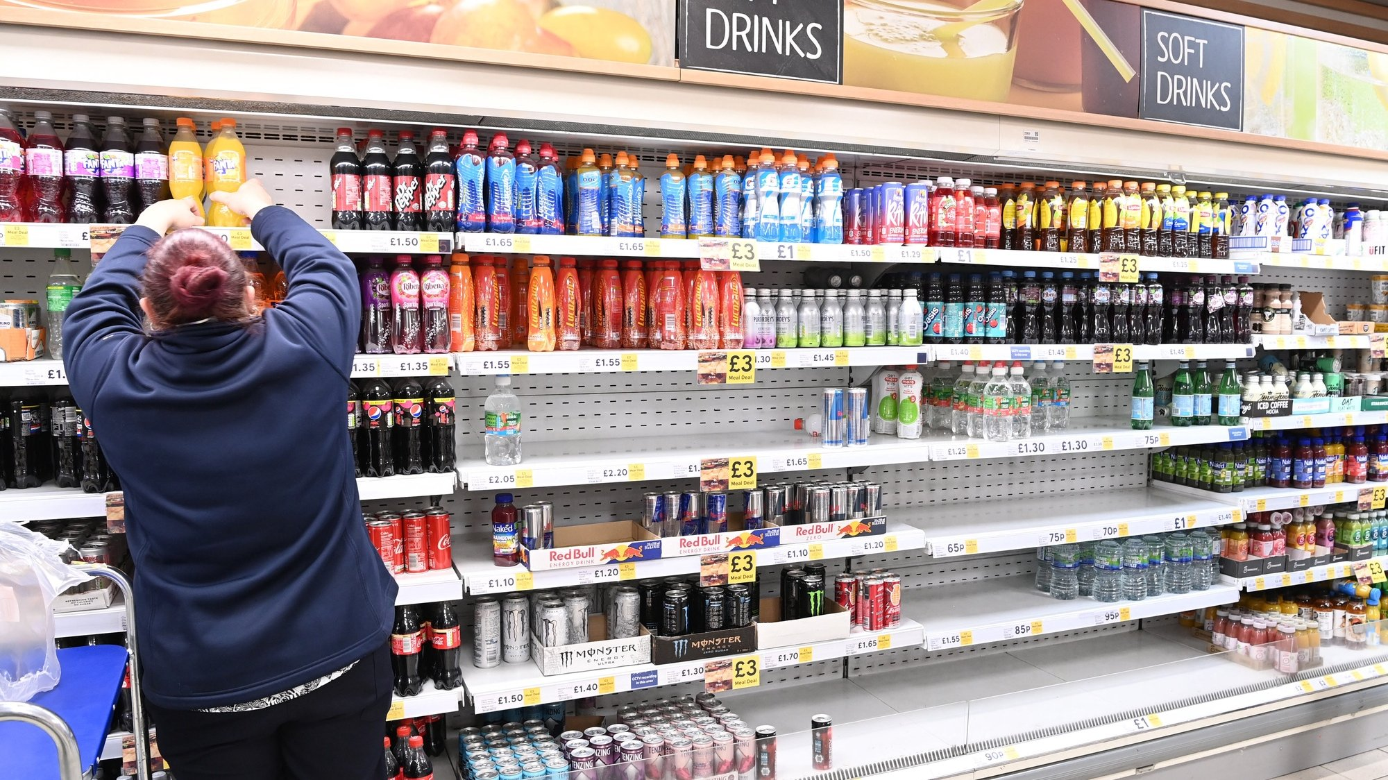 epa09358554 A supermarket worker stocks soft drinks in London, Britain, 22 July 2021. British supermarkets are struggling to stock shelves as staff shortages take their toll due to the so called 'pingdemic'. With so many staff going into self isolation after being pinged by the NHS app, supermarkets are now under increasing pressure to keep shelves fully stocked. The British government is being urged to allow supermarket staff to be exempt from self-isolation rules.  EPA/FACUNDO ARRIZABALAGA