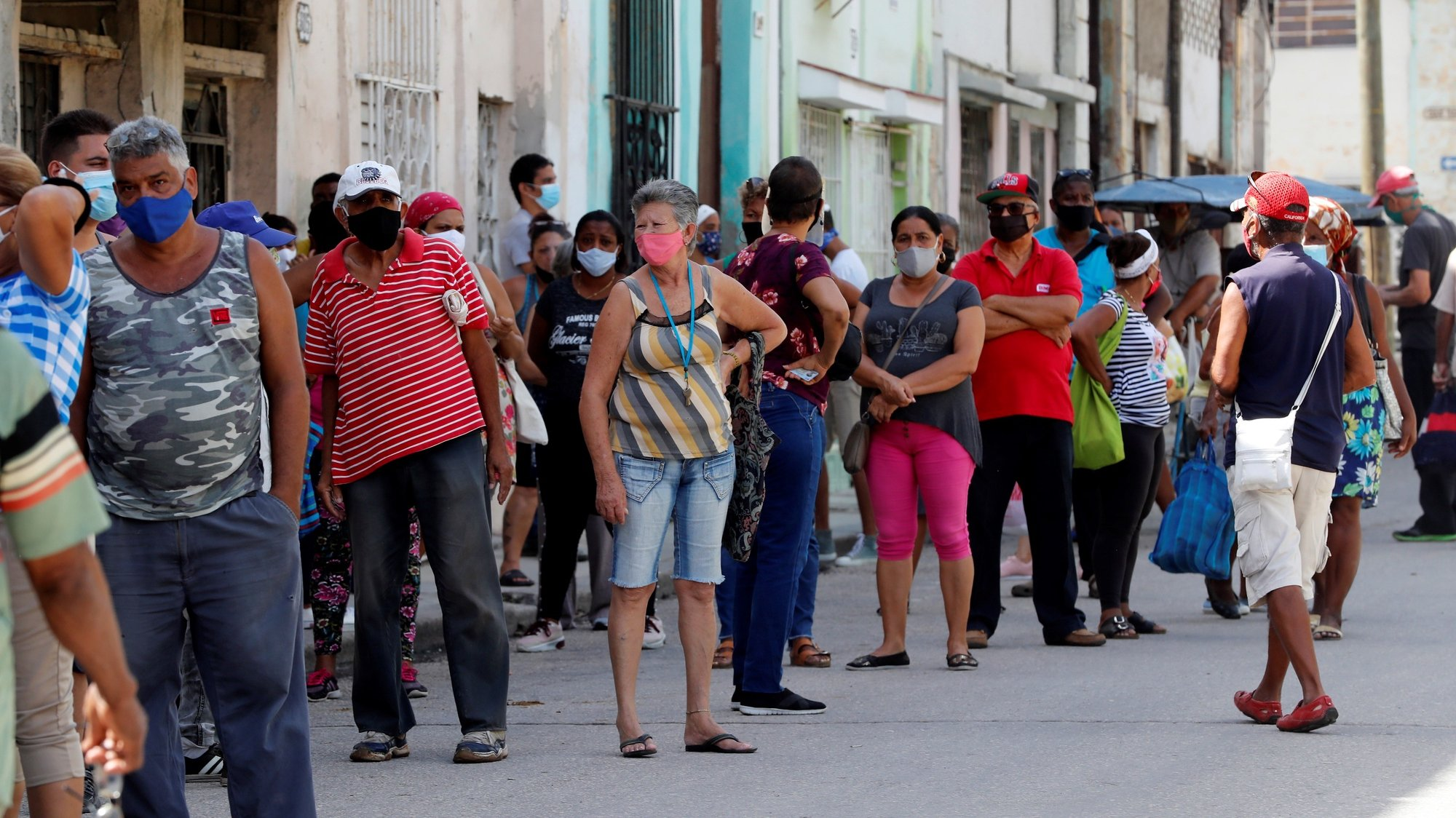 epa09329211 People wear face masks as they queue to enter a market, in Havana, Cuba, on 07 July 2021. Cuba faces a new spike in coronavirus rates, with the Matanzas province suffering the worst part and close to health facilities collapse.  EPA/Ernesto Mastrascusa