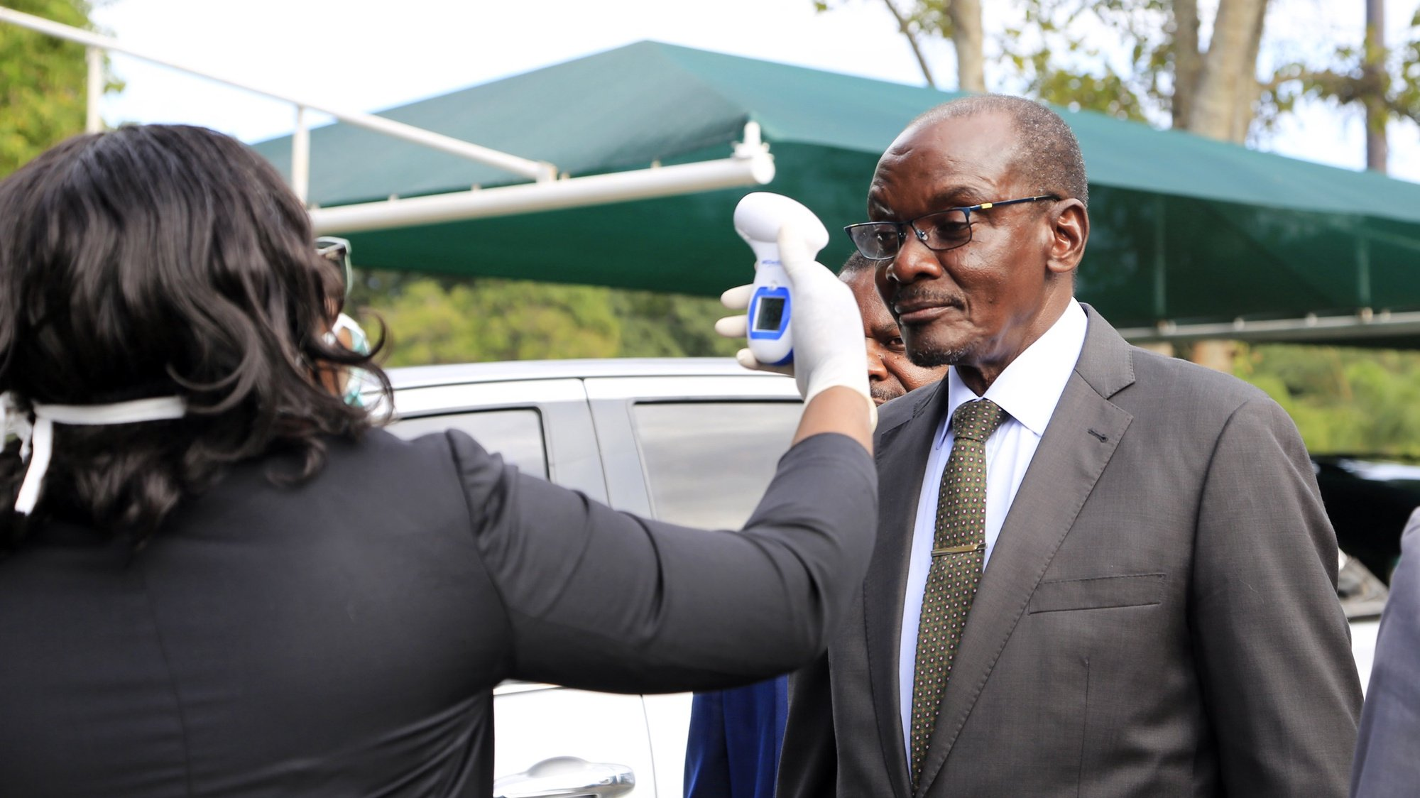 epa08306463 A health officer checks a temerature of Zimbabwean co vice president Kembo Mohadi  (C) before Zimbabwe's President Emmerson Mnangagwa speech at the launch of the Covid -19  Preparedness and Response Plan at the State House in Harare, Zimbabwe, 19 March 2020. There is no confirmed case of COVID-19 in Zimbabwe yet. Countries around the world are taking increased measures to prevent the wide spread of the SARS-CoV-2 Coronavirus causing the Covid-19 disease.  EPA/AARON UFUMELI