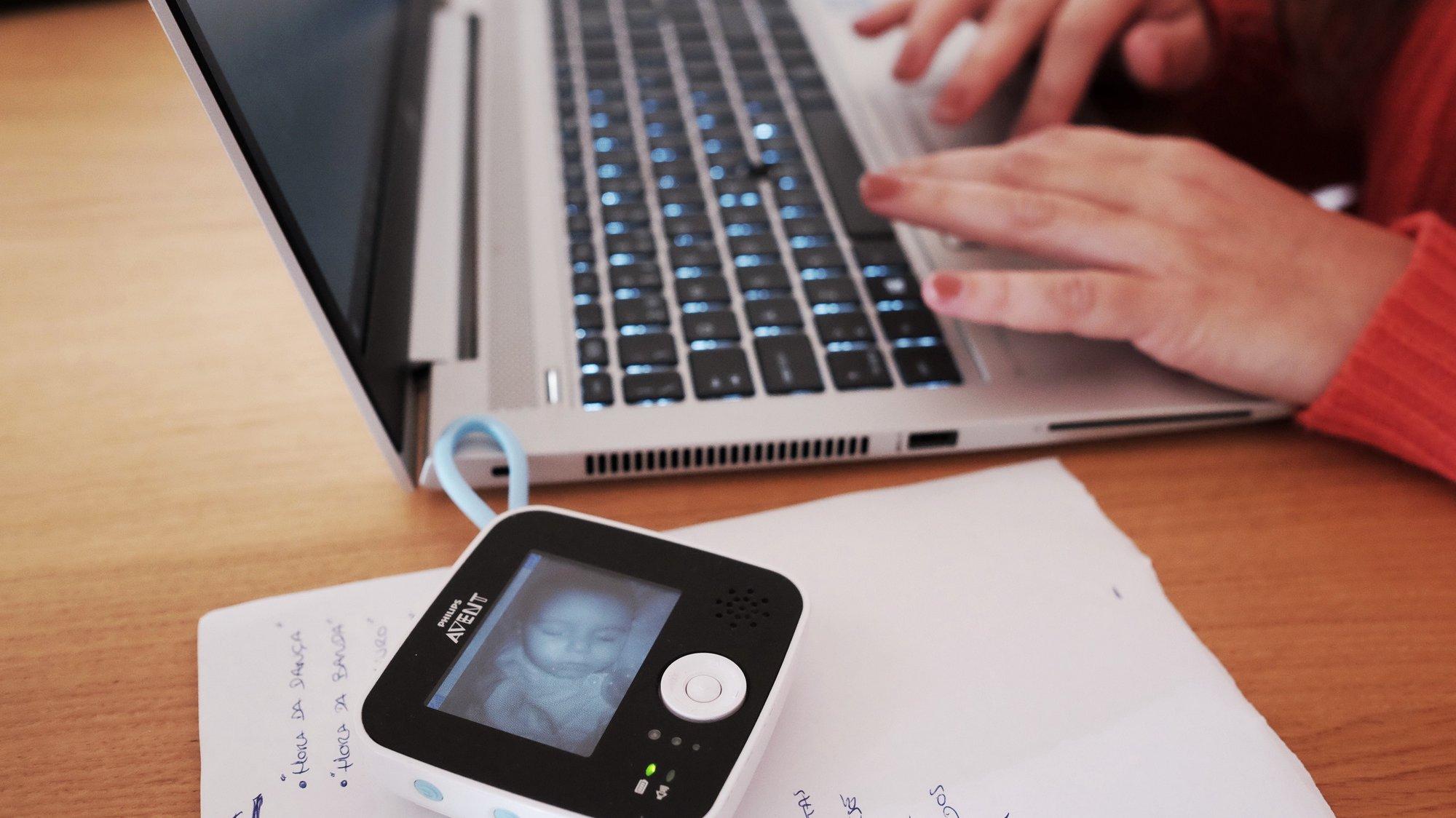 Uma mulher trabalha em casa como seu computador, enquanto monitoriza com um intercomunicador o seu bebé a dormir, no Estoril, 16 de março de 2020. JOSÉ SENA GOULÃO/LUSA