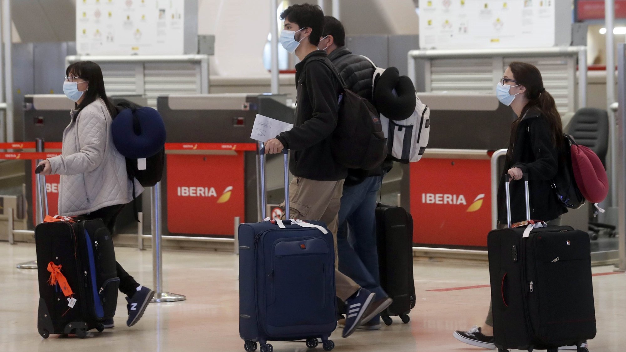 epa08292236 Passengers wearing face masks walk with their baggage at the Adolfo Suarez Madrid-Barajas Airport in Madrid, Spain, 13 March 2020. Morocco has closed its border with Spain amid the ongoing pandemic of the COVID-19 disease caused by the SARS-CoV-2 coronavirus.  EPA/JJ GUILLEN