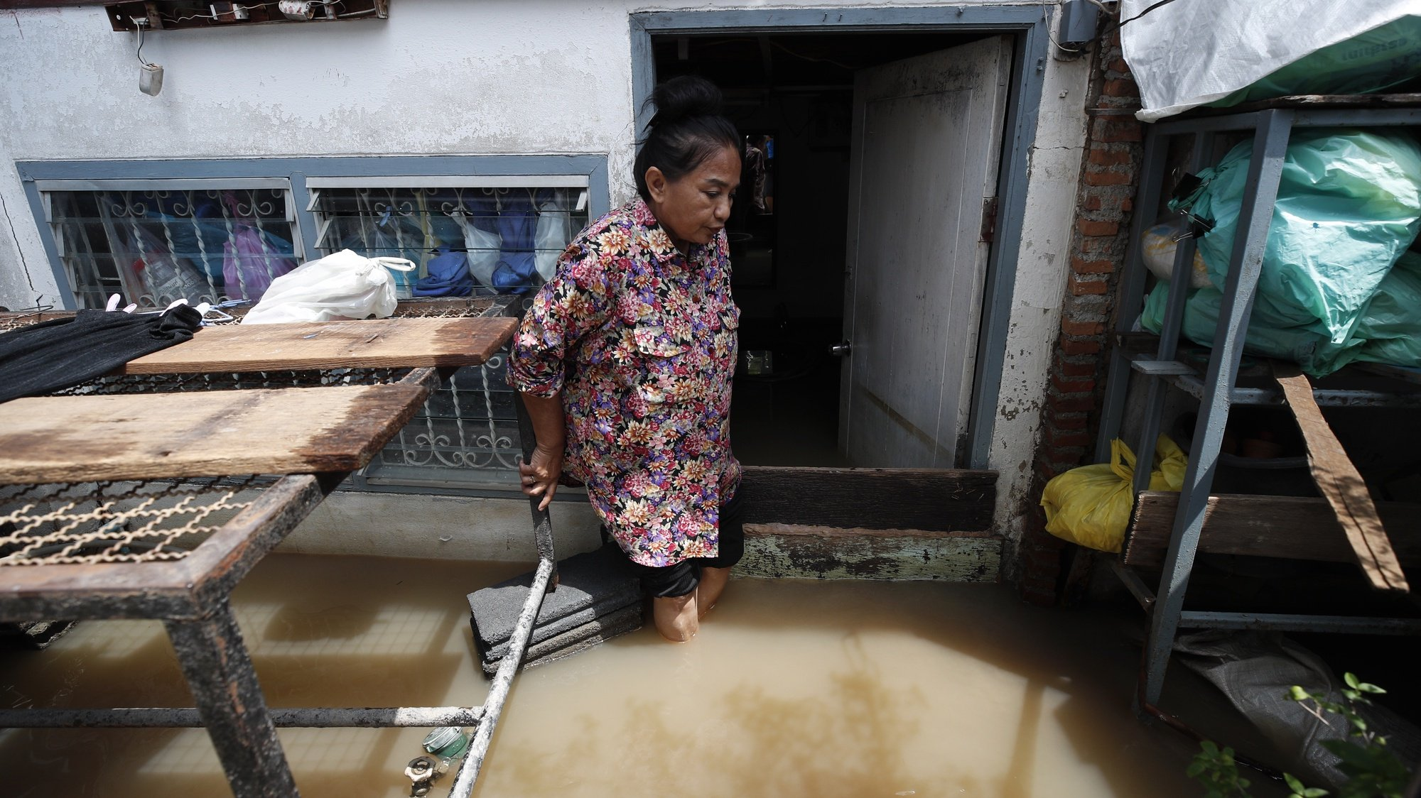 epa09506891 A Thai villager leaves her flooded house at a community in Koh Kret, Nonthaburi neighboring province of Bangkok, Thailand, 05 October 2021. Flooding caused by tropical storm Dianmu has swamped 32 provinces in several parts of Thailand, killed at least eight people and more than two hundreds thousands households have been affected, according to the Disaster Prevention and Mitigation Department.  EPA/RUNGROJ YONGRIT