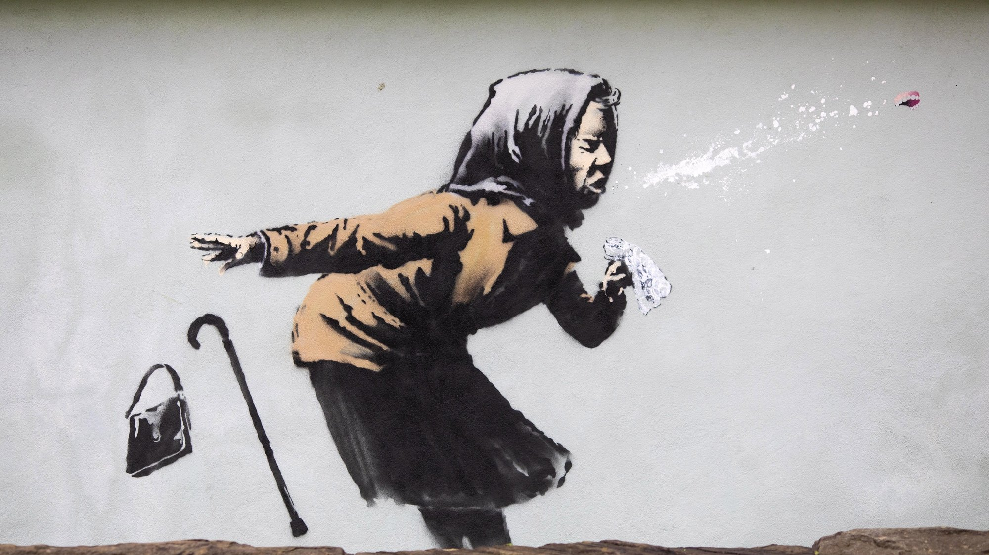 epa08875124 A view of the new creation entitled 'Aachoo!!' by British street artist Banksy that appeared on Vale Street overnight in Bristol, Britain, 10 December 2020. The painting depicts an old woman sneezing with her false teeth flying out.  EPA/JON ROWLEY