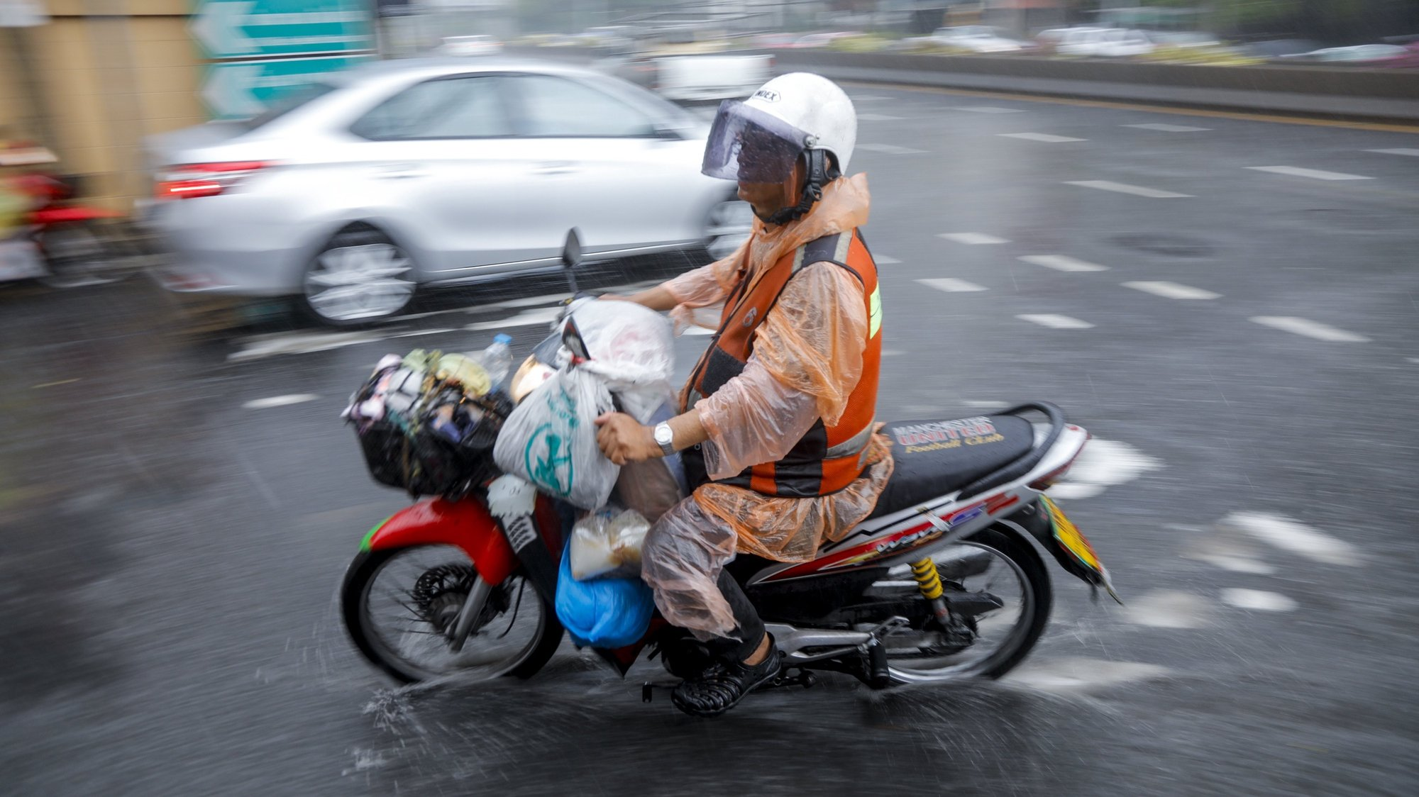 epaselect epa05969493 A motorcycle taxi drives through a puddle of rain water during heavy summer storm in Bangkok, Thailand, 17 May 2017. Thailand's Meteorological Department warned of heavy to very heavy rain in upper Thailand as well as a strong wind wave in the Andaman Sea.  EPA/DIEGO AZUBEL