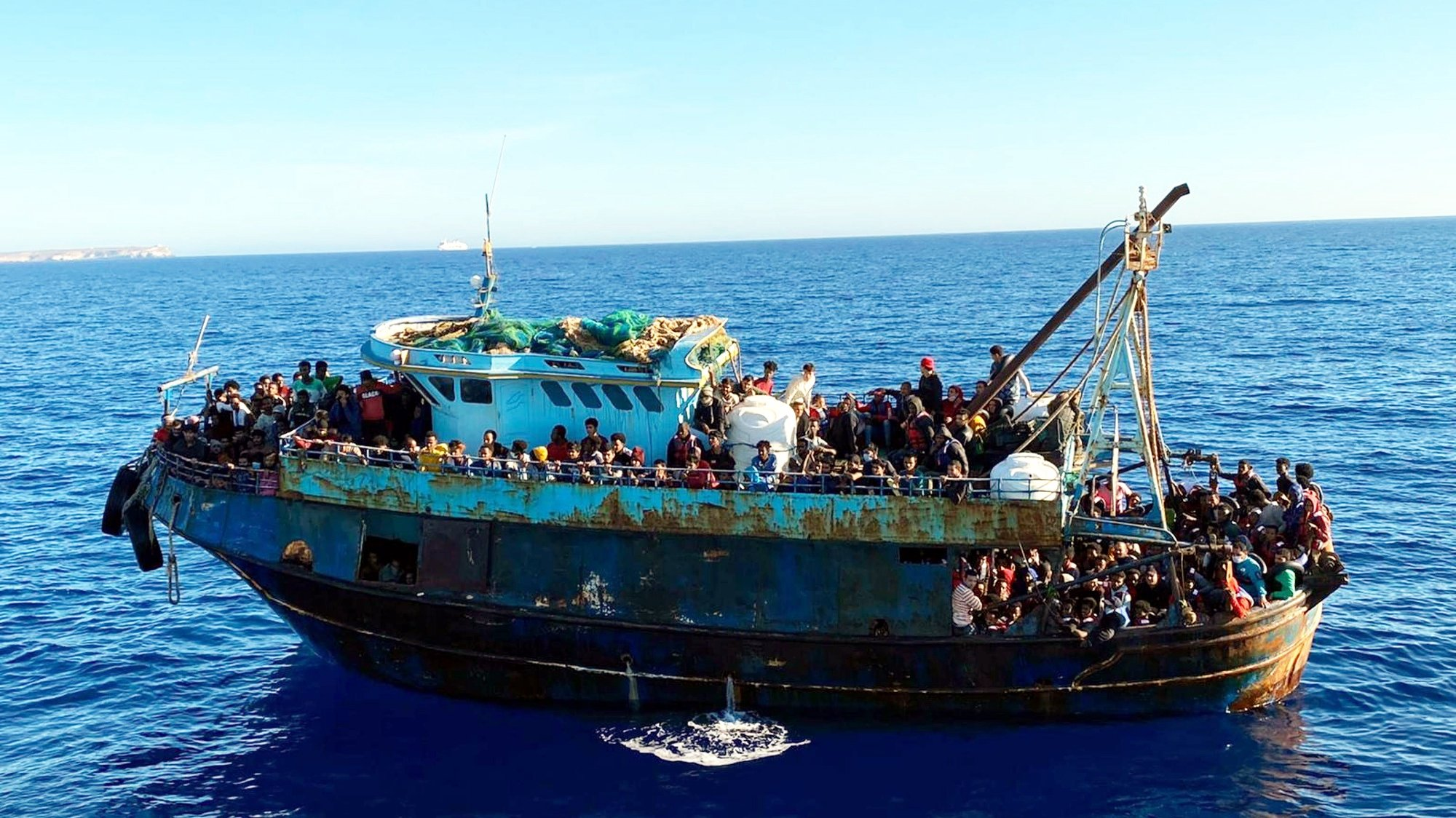 epa09187028 One of the two boats with a total of 415 migrants on board, in Lampedusa, Italy, 09 May 2021. The first wooden boat of 20 meters length, with 325 people on board, was intercepted eight miles off Lampedusa and the second one five miles off the coast and escorted by a security forces patrol boat to Favaloro Pier. On board were 90 migrants of different nationalities, 83 men, 6 women and a newborn baby.  EPA/ANSA