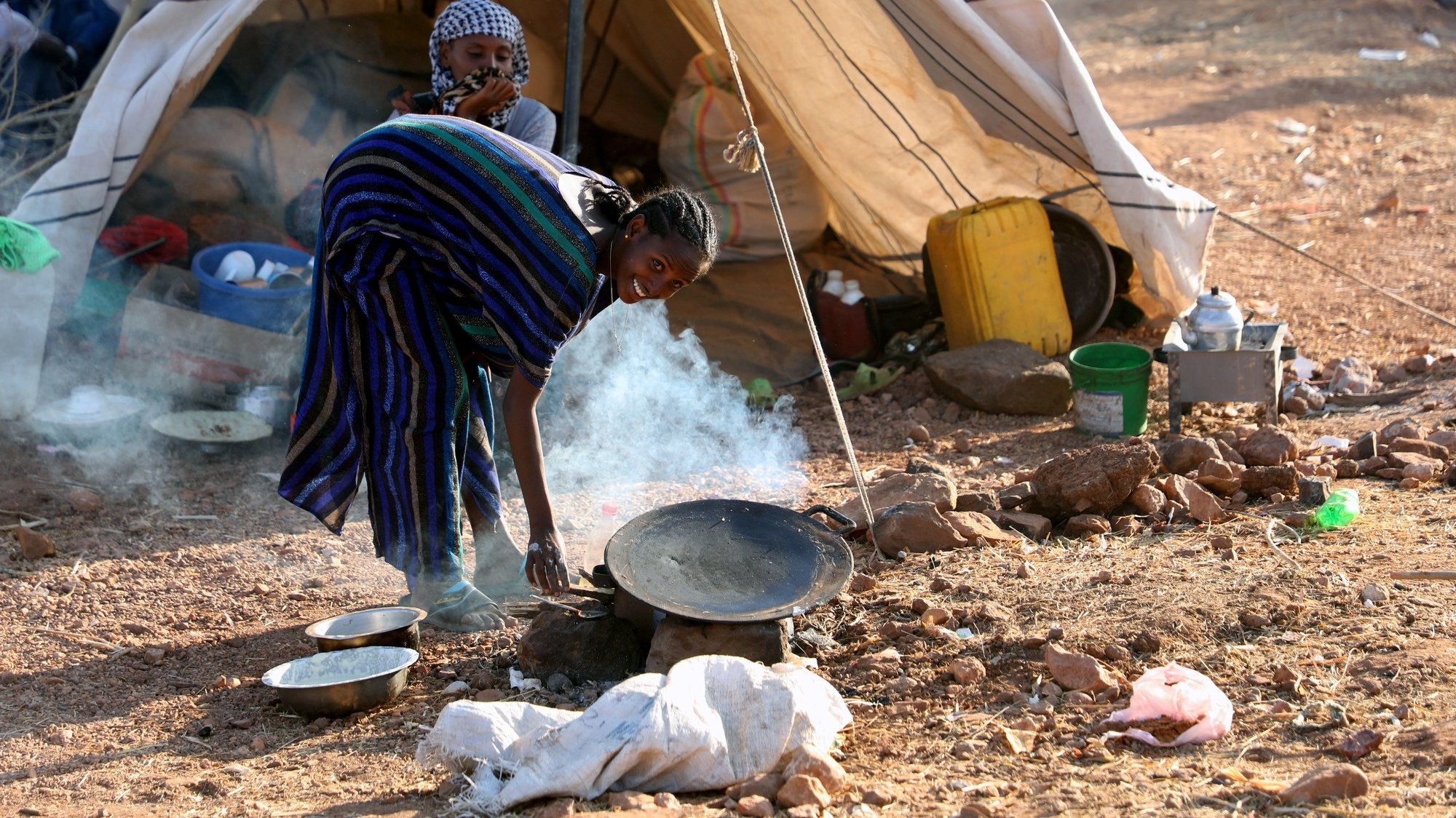 epa08849891 A woman preparing a meal outside her temporary shelter at Um Rakuba refugee camp in the state of al-Qadarif (also known as Gedaref), Sudan, 28 November 2020. The number of refugees in this camp reached nearly 10,000 refugees who crossed the border from Ethiopia to Sudan to escape the conflict in Tigray region of Ethiopia.  EPA/MOHAMMED ABU OBAID