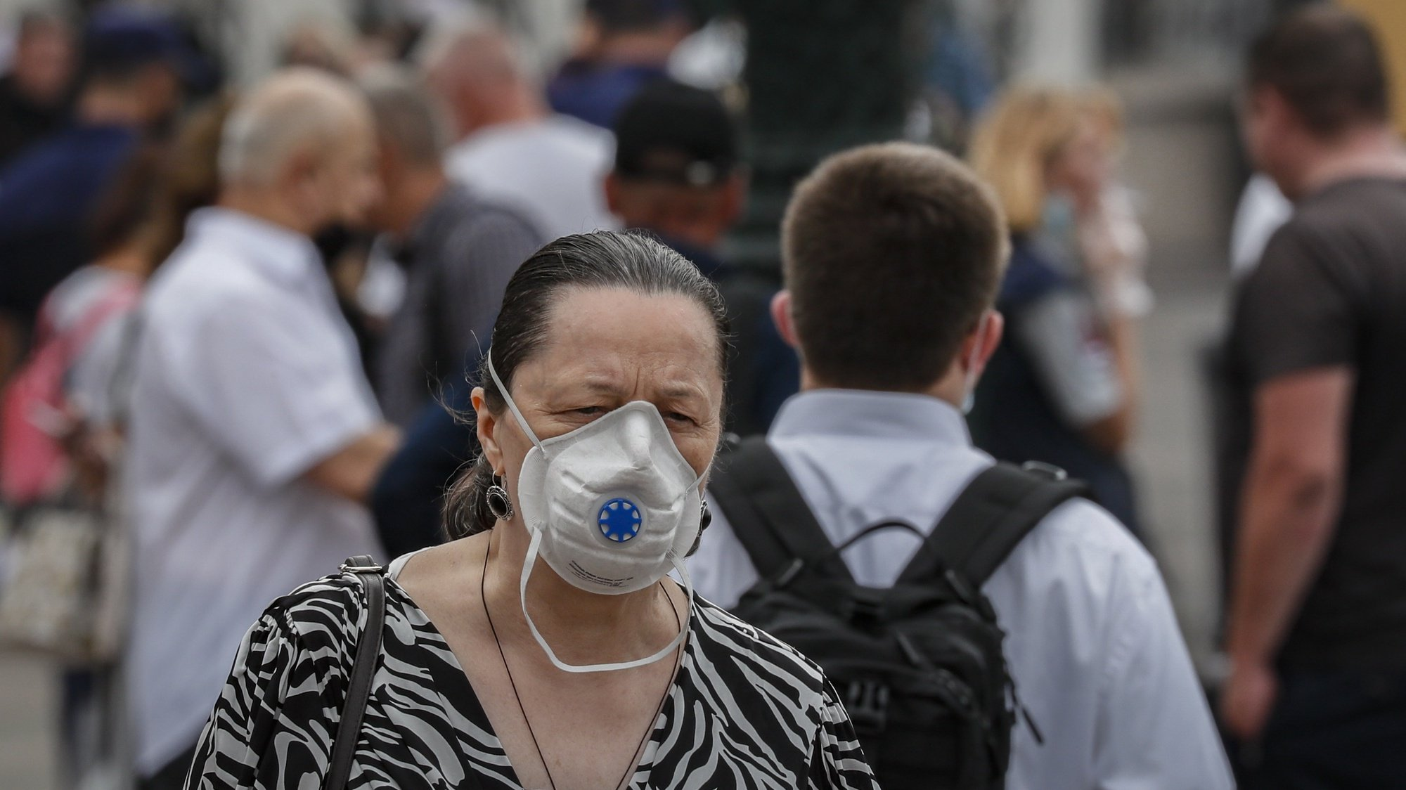 epa09380264 Russian woman wearing a protective face mask on the street in Moscow, Russia 30 July 2021. Moscow Mayor Sergei Sobyanin has canceled the obligation to wear gloves in public places. At the same time, wearing masks remain mandatory during Covid-19 pandemic.  EPA/YURI KOCHETKOV