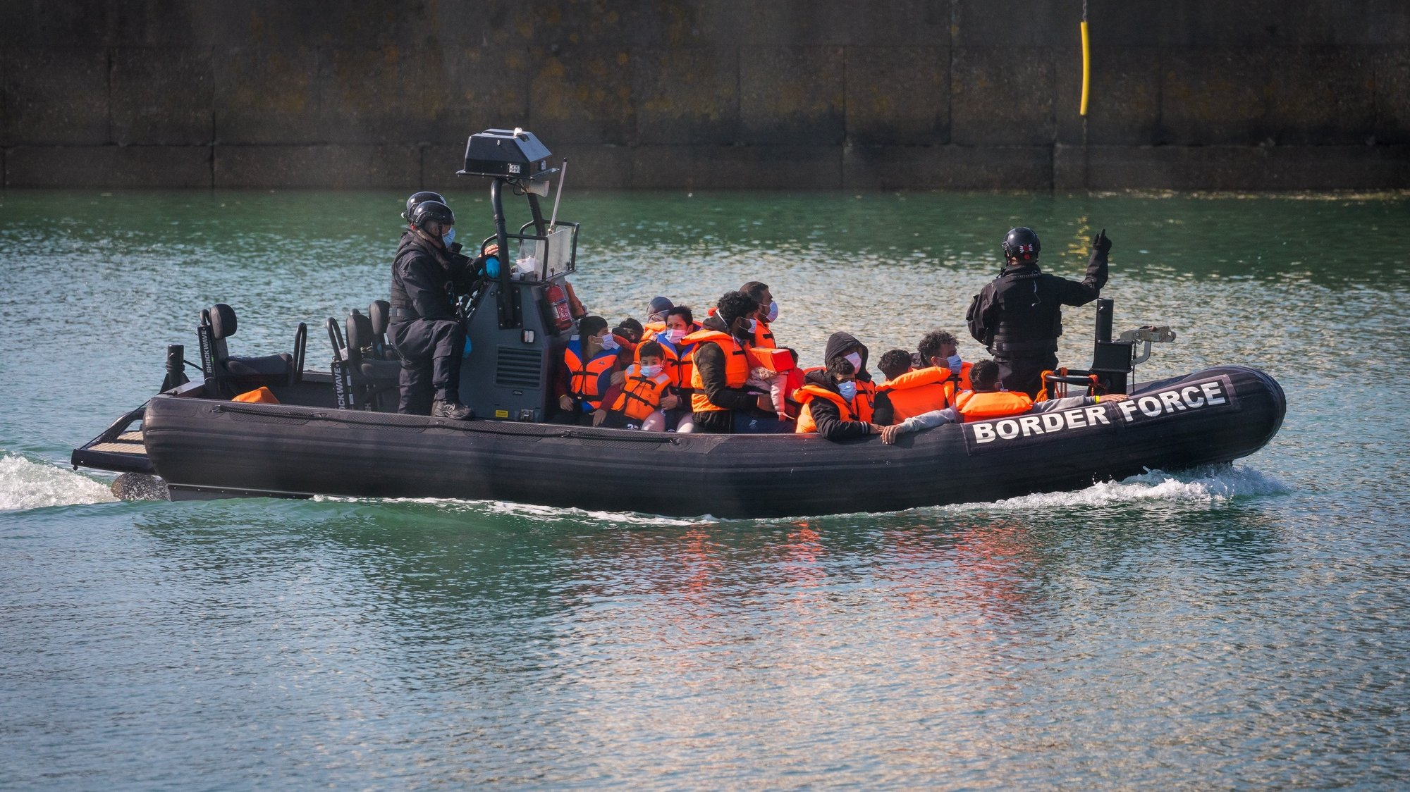epa09358012 A boat from Britain's Border Force (BF) transports a group of people thought to be migrants, including children, who were found in the English Channel off the coast of Dover, in Dover, Kent, Britain, 22 July 2021. Britain and France are continuing ongoing talks in a bid to resolve the migrant crisis in the English Channel as migrants continue to arrive along the coast of the UK in their quest for asylum.  EPA/VICKIE FLORES