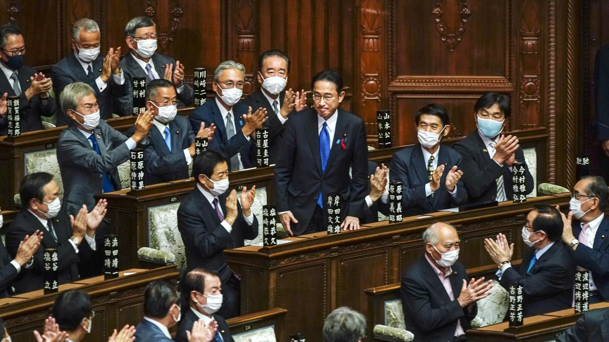 epa09504875 Fumio Kishida (C) is celebrated by his fellow lawmakers after being elected as new Prime Minister, during the general assembly of an extraordinary parliamentary session in Tokyo, Japan, 04 October 2021.  EPA/KIMIMASA MAYAMA
