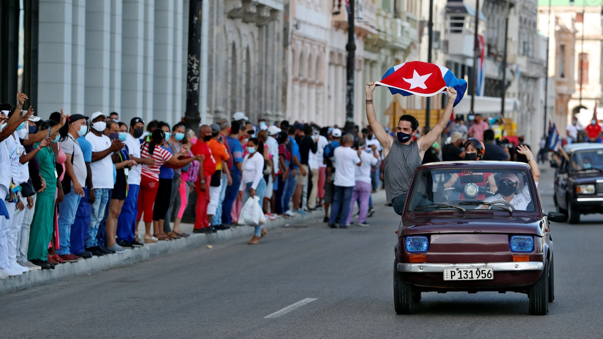 epa09398551 A person waves a Cuban flag during a march in support of the Cuban revolution through the Malecon area in Havana, Cuba, 05 August 2021. Cubans took to the streets in Cuba on 11 July to protest the government response to the COVID-19 pandemic, shortages of medicines and basic commodities, and decliing infrustructure on the island nation.  EPA/Ernesto Mastrascusa