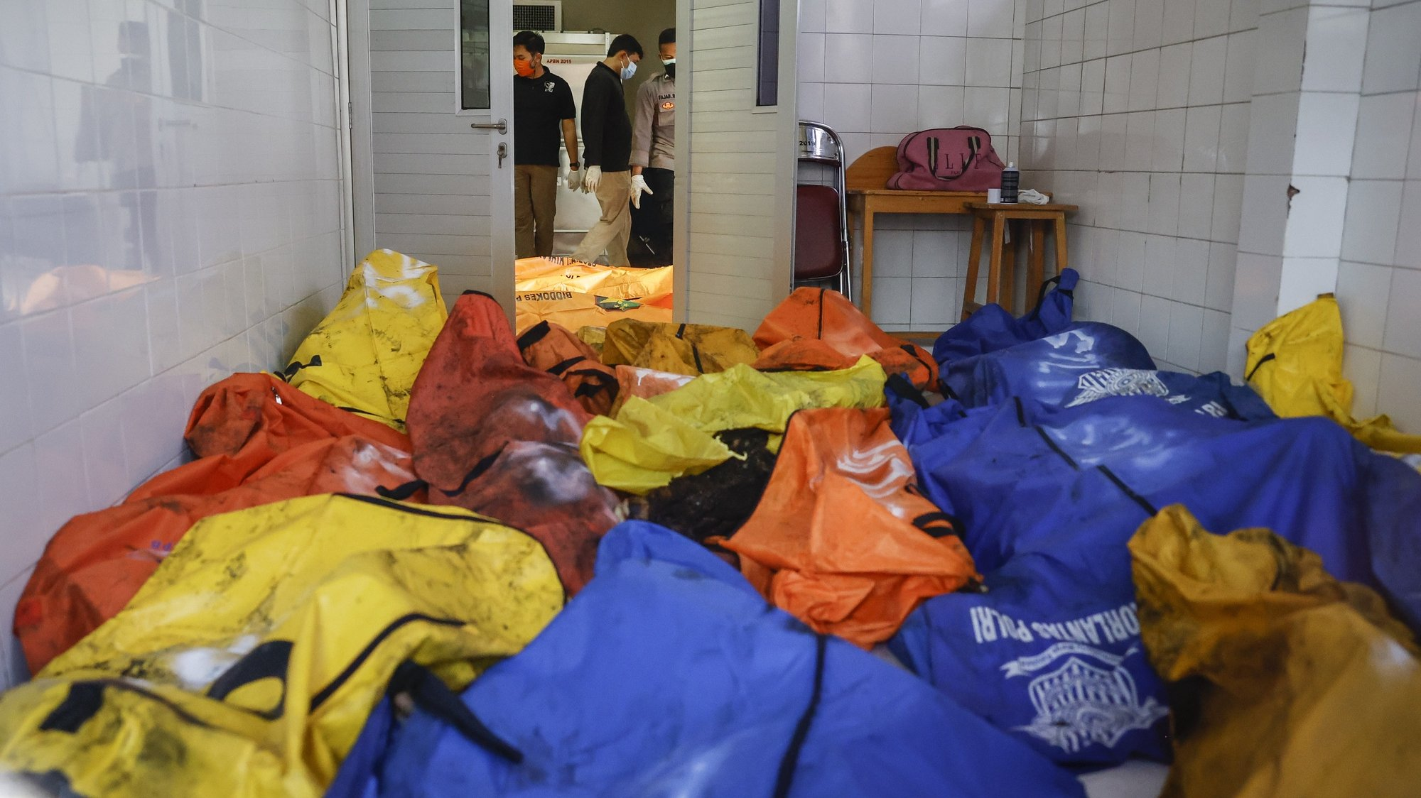 epa09454476 Disaster Victims Identification (DVI) police officers inspect body bags in the aftermath of a prison fire, at a hospital in Tangerang, Banten, Indonesia, 08 September 2021. A fire broke out in a prison in Tangerang killing at least 41 people and injuring dozens.  EPA/MAST IRHAM