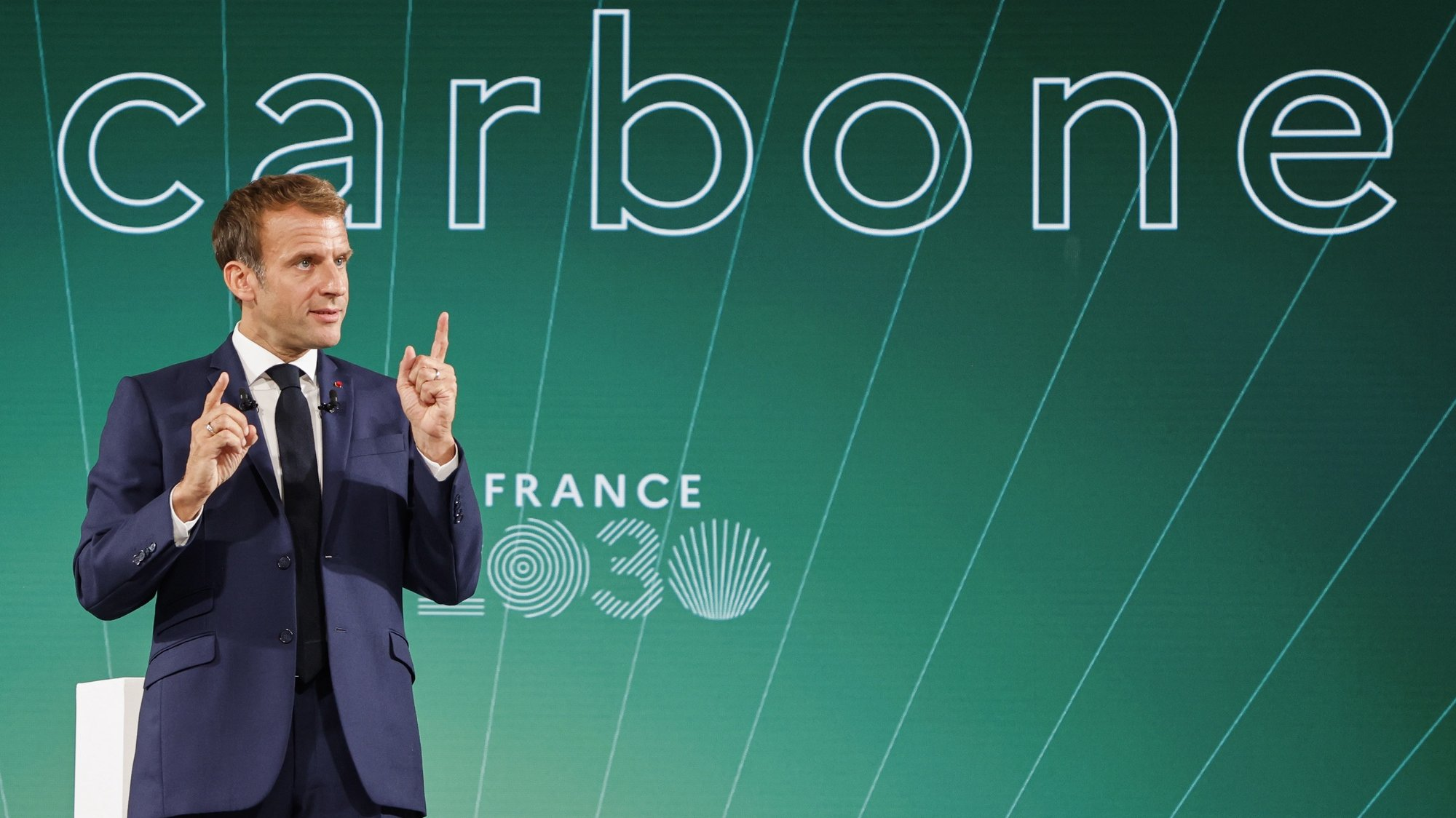 """epa09519734 France's President Emmanuel Macron speaks in front of a screen with the word """"Carbon"""" during the presentation of """"France 2030"""" investment plan at The Elysee Presidential Palace in Paris, France, 12 October 2021. Hydrogen, semiconductors or electric batteries: French President Macron details on 12 October 2021 the priority sectors of the """"France 2030"""" plan to """"bring out the champions of tomorrow"""", in the face of Chinese and American competition and criticism of the """"decline"""" of France.  EPA/LUDOVIC MARIN / POOL  MAXPPP OUT"""