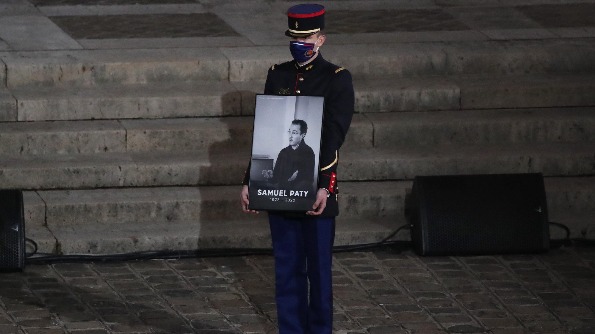 epa08762704 A Republican Guard holds a portrait of Samuel Paty in the courtyard of the Sorbonne university during a national memorial event, in Paris, France, 21 October 2020. French history teacher Samuel Paty was beheaded in Conflans-Sainte-Honorine, northwest of Paris, by a 18-year-old Moscow-born Chechen refugee, who was later shot dead by police.  EPA/Francois Mori / POOL MAXPPP OUT