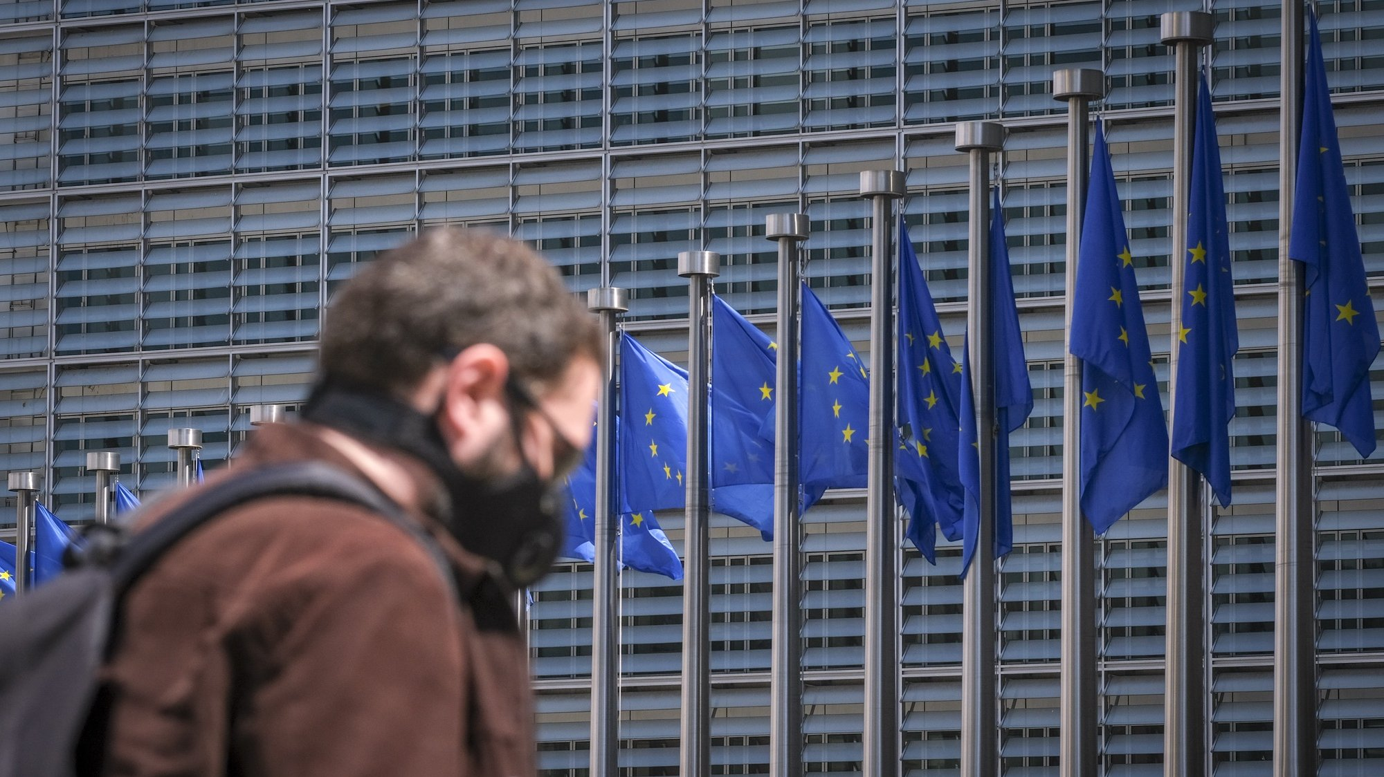 epa08443018 A man wearing a face mask walks in front of the European Commission flags at the Berlaymont building headquarters in Brussels, Belgium, 25 May 2020. Countries around the world are gradually easing COVID-19 lockdown restrictions in an effort to restart the economy and help people in their daily routines.  EPA/OLIVIER HOSLET