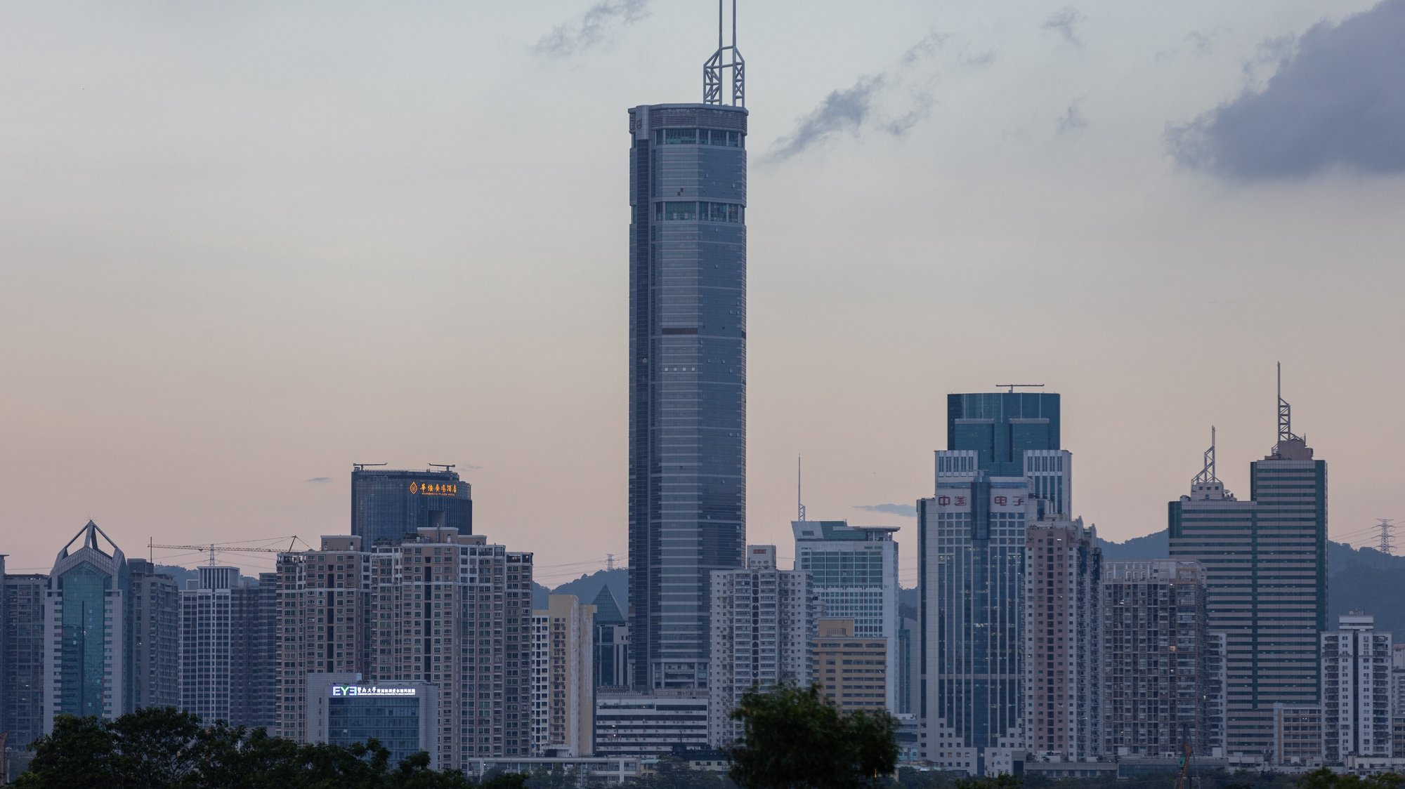 epa09208452 The near 300-metre high SEG Plaza (C) stands in Shenzhen as seen from Hong Kong, China, 18 May 2021. The skyscraper was evacuated earlier after it began to shake.  EPA/JEROME FAVRE