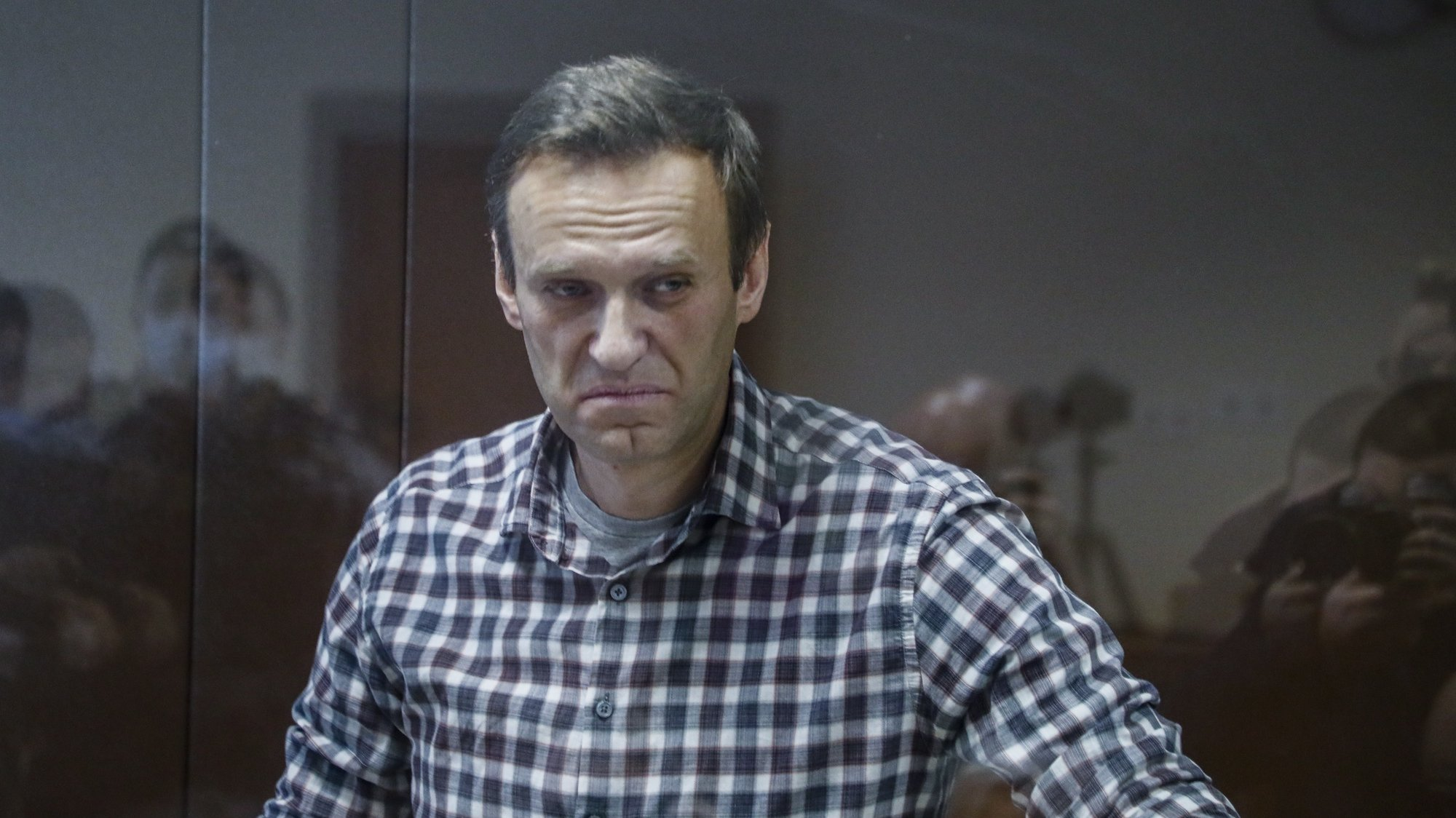 epa09025232 Russian opposition leader Alexei Navalny stands inside a glass cage prior to a hearing at the Babushkinsky District Court in Moscow, Russia, 20 February 2021. The Moscow City court will hold a visiting session at the Babushkinsky District Court Building to consider Navalny's lawyers appeal against a court verdict issued on 02 February 2021, to replace the suspended sentence issued to Navalny in the Yves Rocher embezzlement case with an actual term in a penal colony.  EPA/YURI KOCHETKOV MANDATORY CREDIT