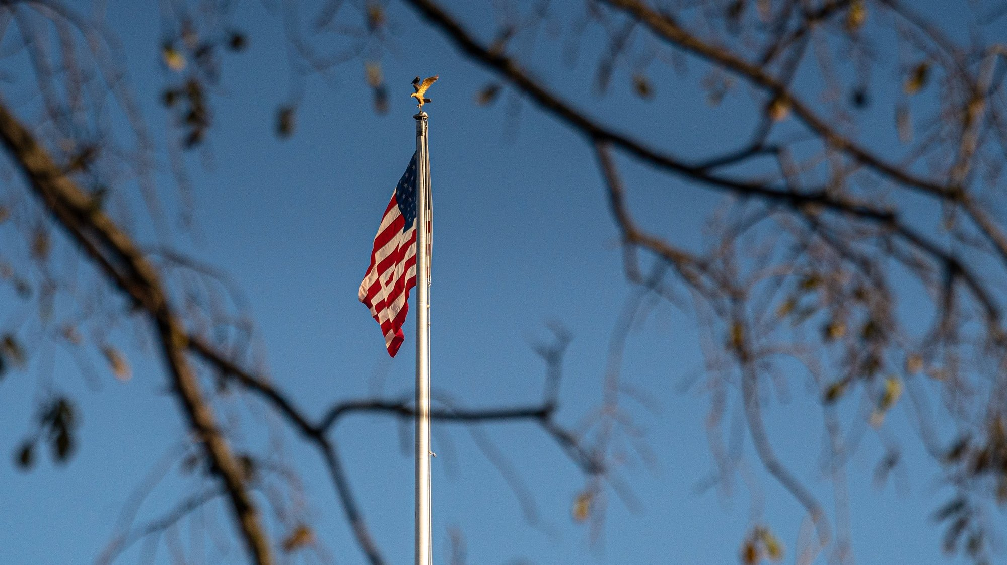 epa08824340 The US flag is seen waving in the wind as the trees lose their leaves in the fall season in Washington, DC, USA, on 16 November 2020.  EPA/Ken Cedeno / POOL