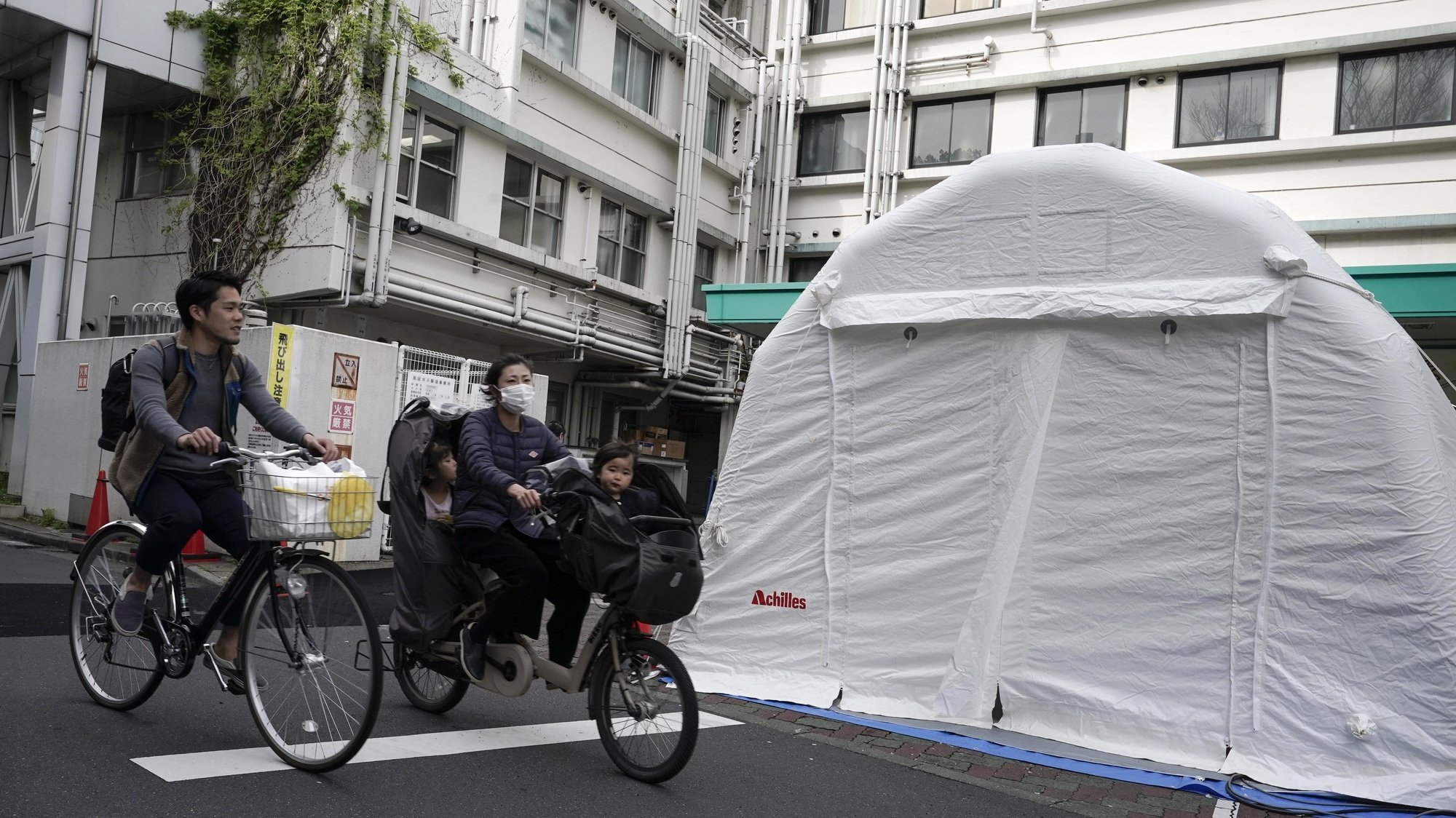 epa08374699 A family cycles past tents for COVID-19 testing outside Kawakita General Hospital in Tokyo, Japan, 21 April 2020. Japan has recently witnessed a sharp rise in infections. Prime Minister Shinzo Abe declared on 16 April 2020 a nationwide state of emergency. According to media reports, a new wave of COVID-19 infections is threatening the country's healthcare system, with several hospitals forced to turn away sick people.  EPA/KIMIMASA MAYAMA