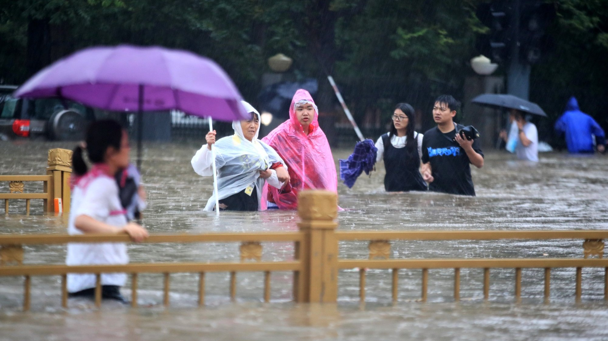 epa09356178 People walk in the flooded road after record downpours in Zhengzhou city in central China's Henan province Tuesday, July 20, 2021 (issued 21 July 2021). Heavy floods in Central China killed 12 in Zhengzhou city due to the rainfall yesterday, 20 July 2021, according to official Chinese media. Over 144,660 people have been affected by heavy rains in Henan Province since July 16, and over 10,000 had to be relocated, the provincial flood control and drought relief headquarters said Tuesday.  EPA/FEATURECHINA CHINA OUT