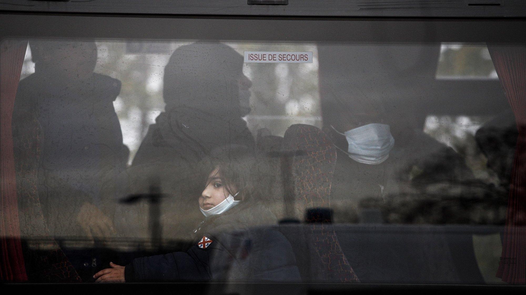 Criança migrante evacuada por autocarro de um campo de refugiados no norte de paris
