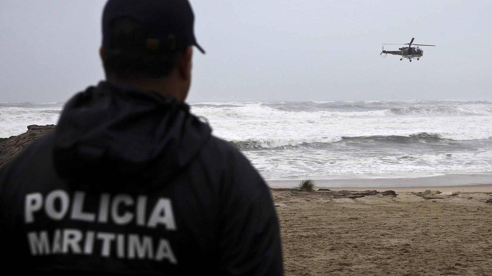 Um elemento da Polícia Marítima observa um helicóptero da Força Aérea