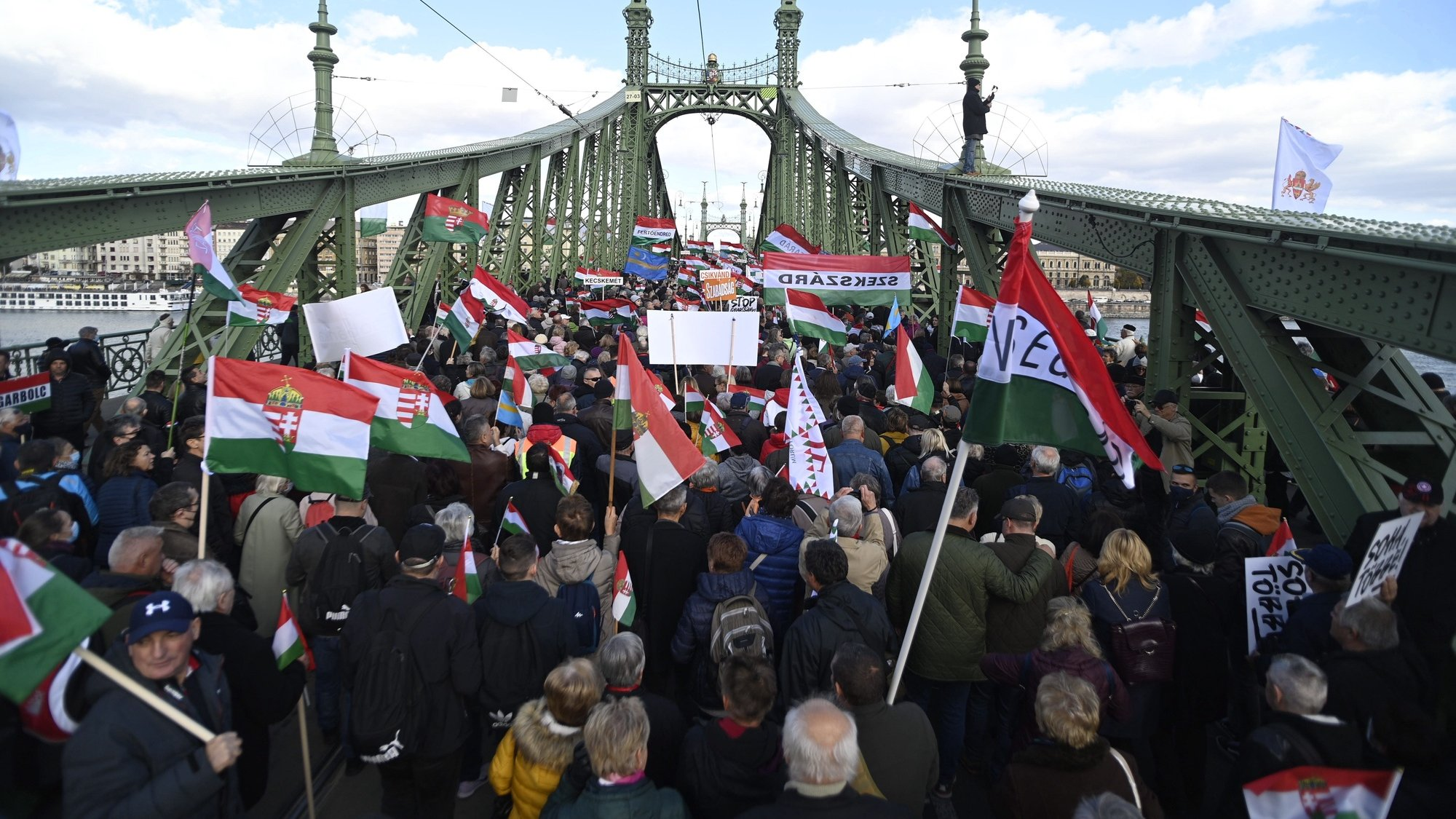 epa09541171 Participants of the Peace March wave flags during the demonstration marking the 65th anniversary of the Hungarian revolution and war of  independence against communist rule and the Soviet Union in 1956 on the Szabadsag (Freedom) Bridge in Budapest, Hungary, 23 October 2021. The Peace March was organized by the pro-government Civic Solidarity Forum Foundation.  EPA/Zoltan Balogh HUNGARY OUT